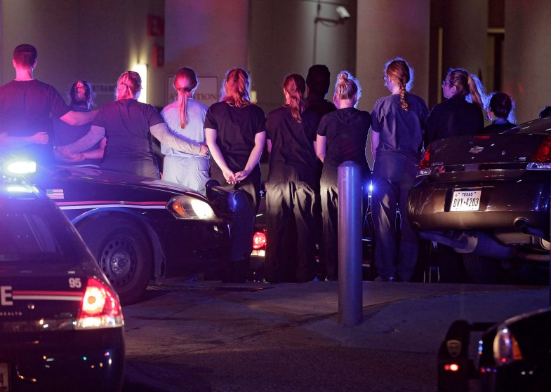 Dallas police officers and hospital staff form a line around the emergency entrance to Baylor Scott & White Hospital as a police officer's body is taken from the facility in Dallas on July 08, 2016.