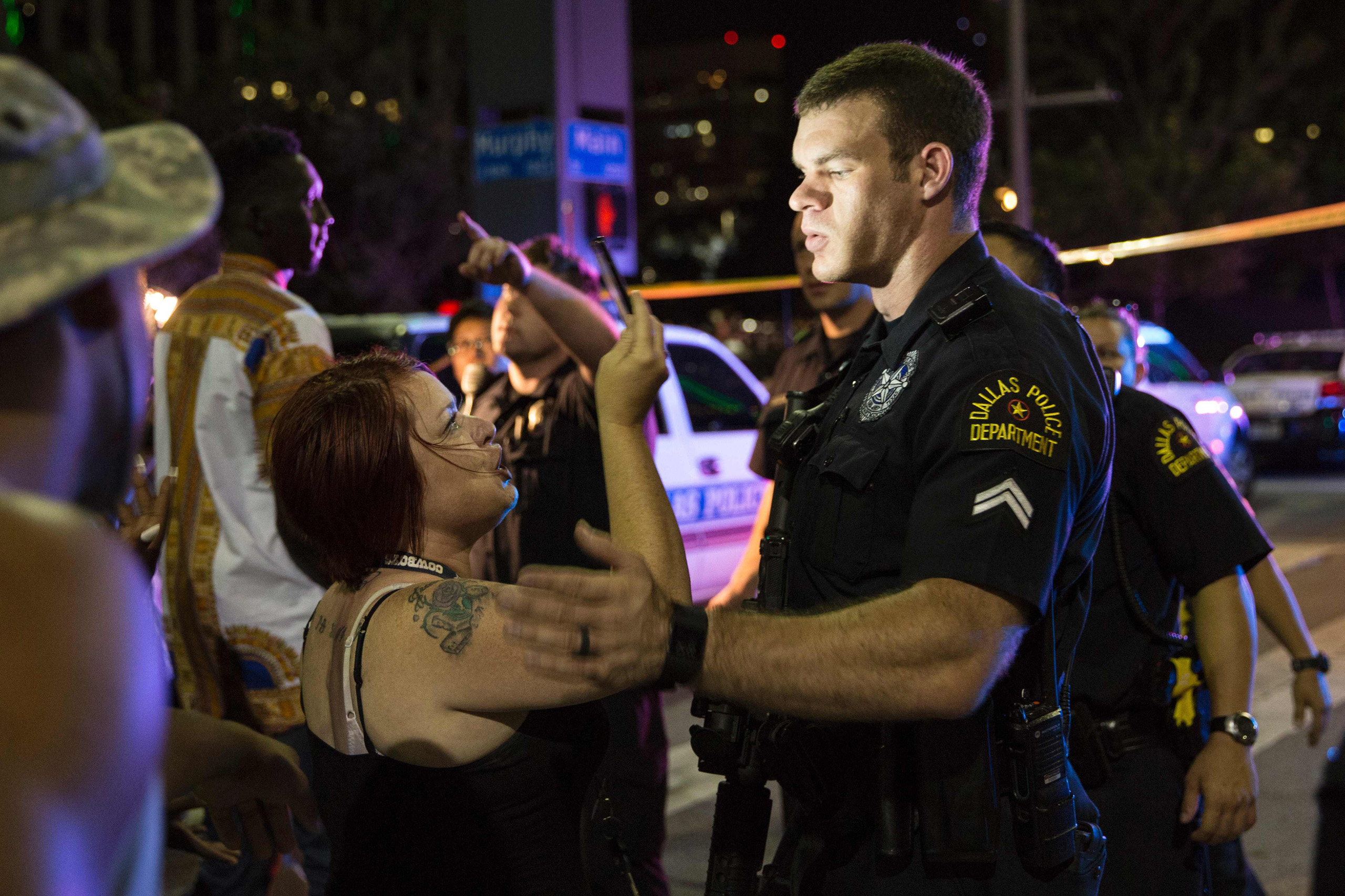Police attempt to calm the crowd as an arrest is made following a sniper shooting in Dallas on July 7, 2016.