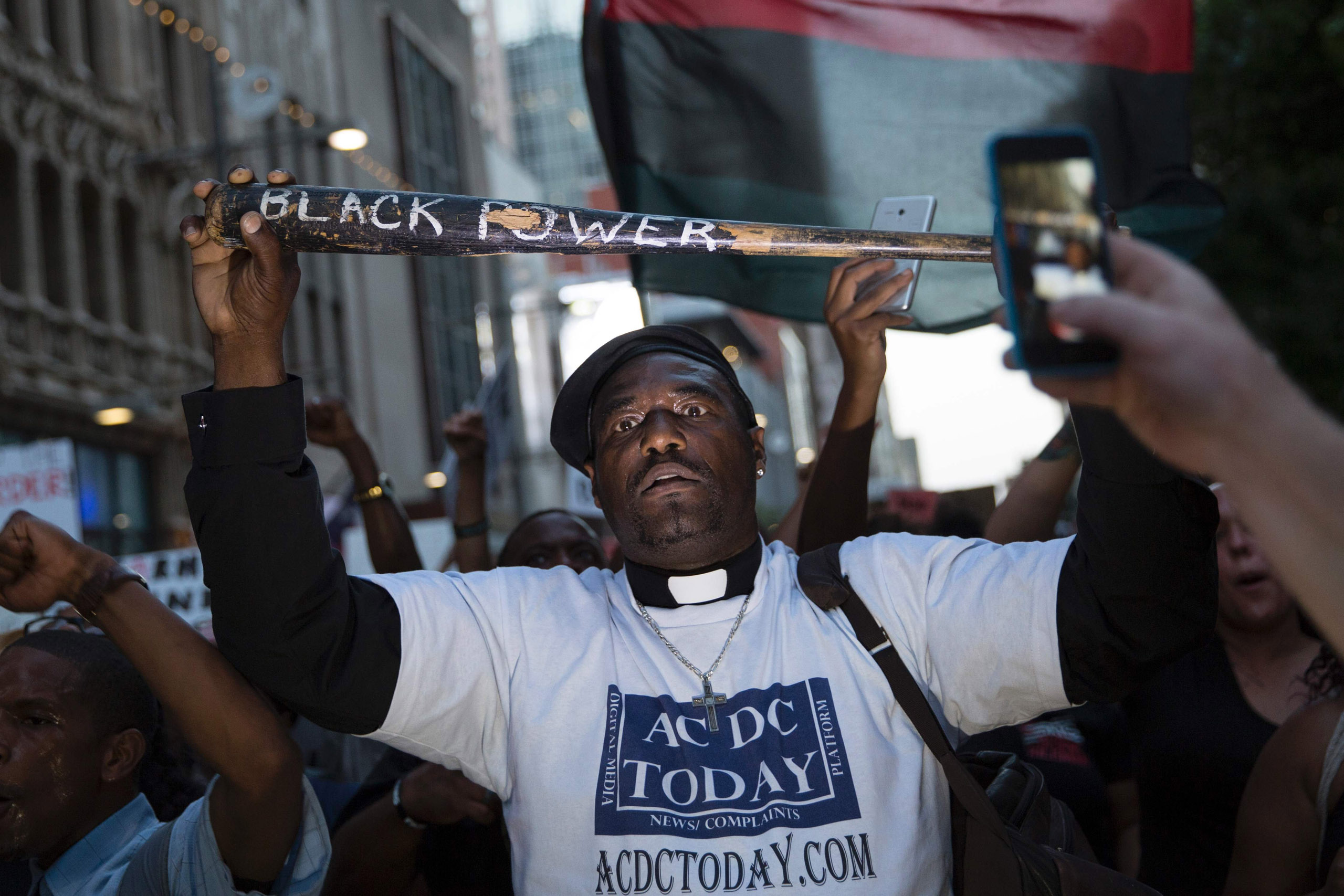 "A man holds a bat reading ""Black Power"" during a protest in Dallas on July 7, 2016."