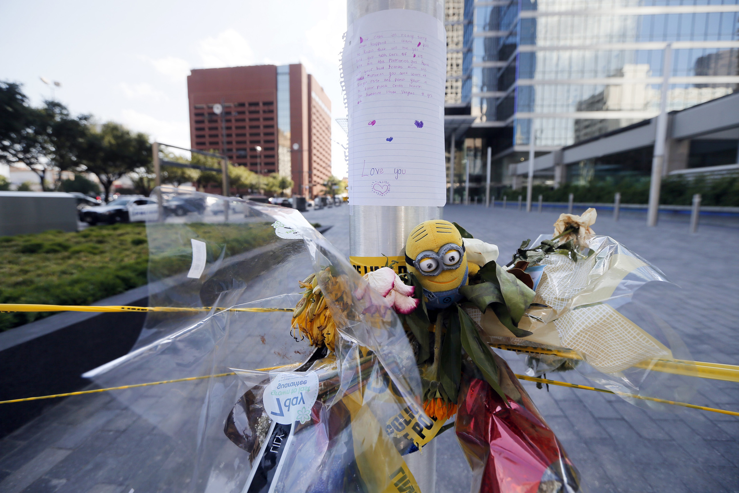 A letter from a child to Dallas police officers sits atop flowers and other items left at a makeshift memorial by the crime scene of Thursday night's shooting in Dallas on July 10, 2016.
