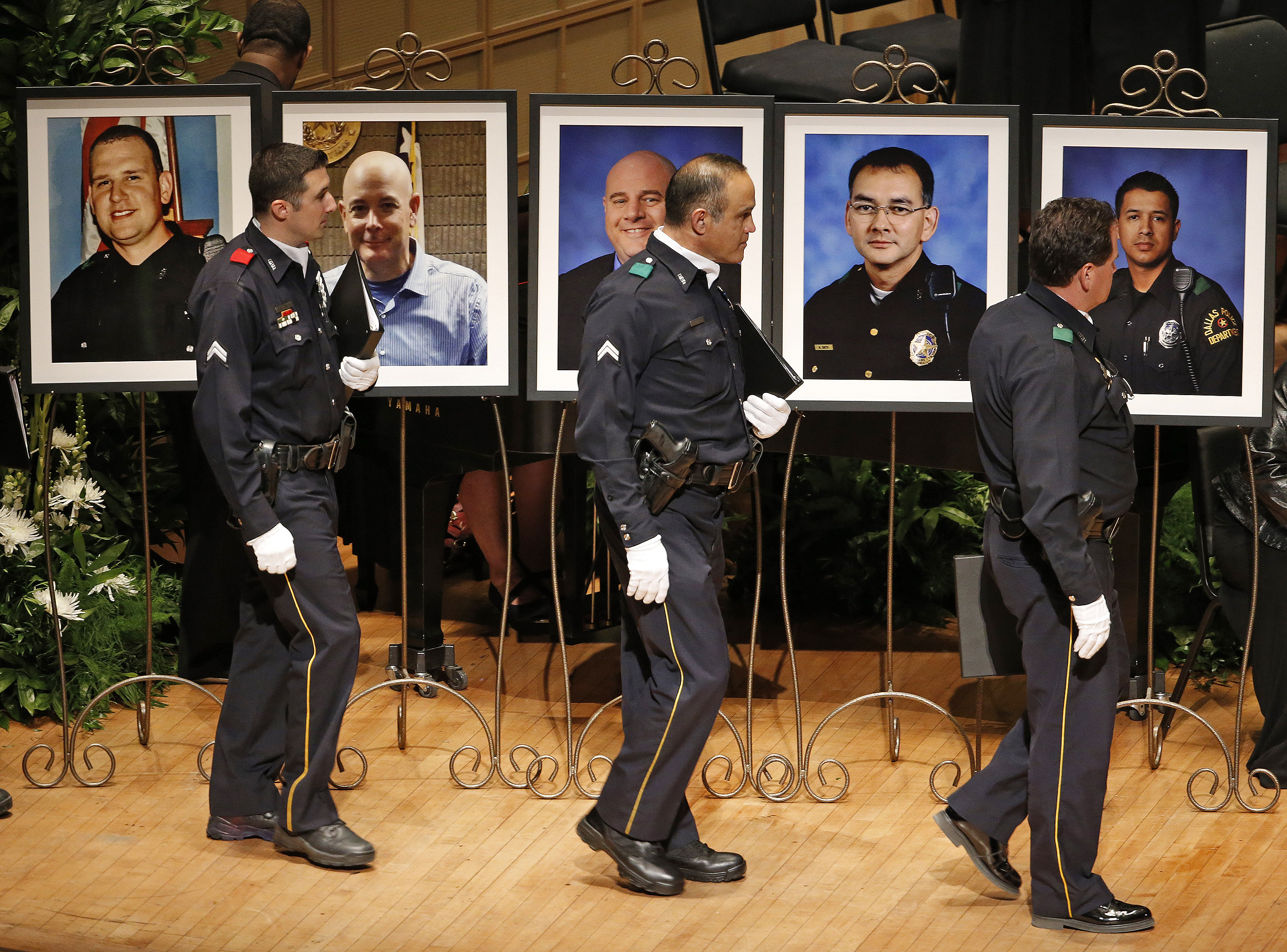 Members of the Dallas Police Department Choir walk past portraits of their fallen comrades during a memorial for five Dallas and DART police officers on July 12, 2016 at the Morton H. Meyerson Symphony Center in Dallas.