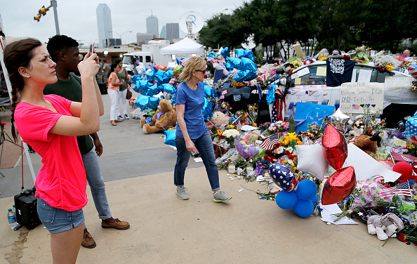Michaela Granello (L), 19, of Red Oak, takes photo of the growing memorial in front of the Jack Evans Police Headquarters building on July 11, 2016 in Dallas, Texas.
