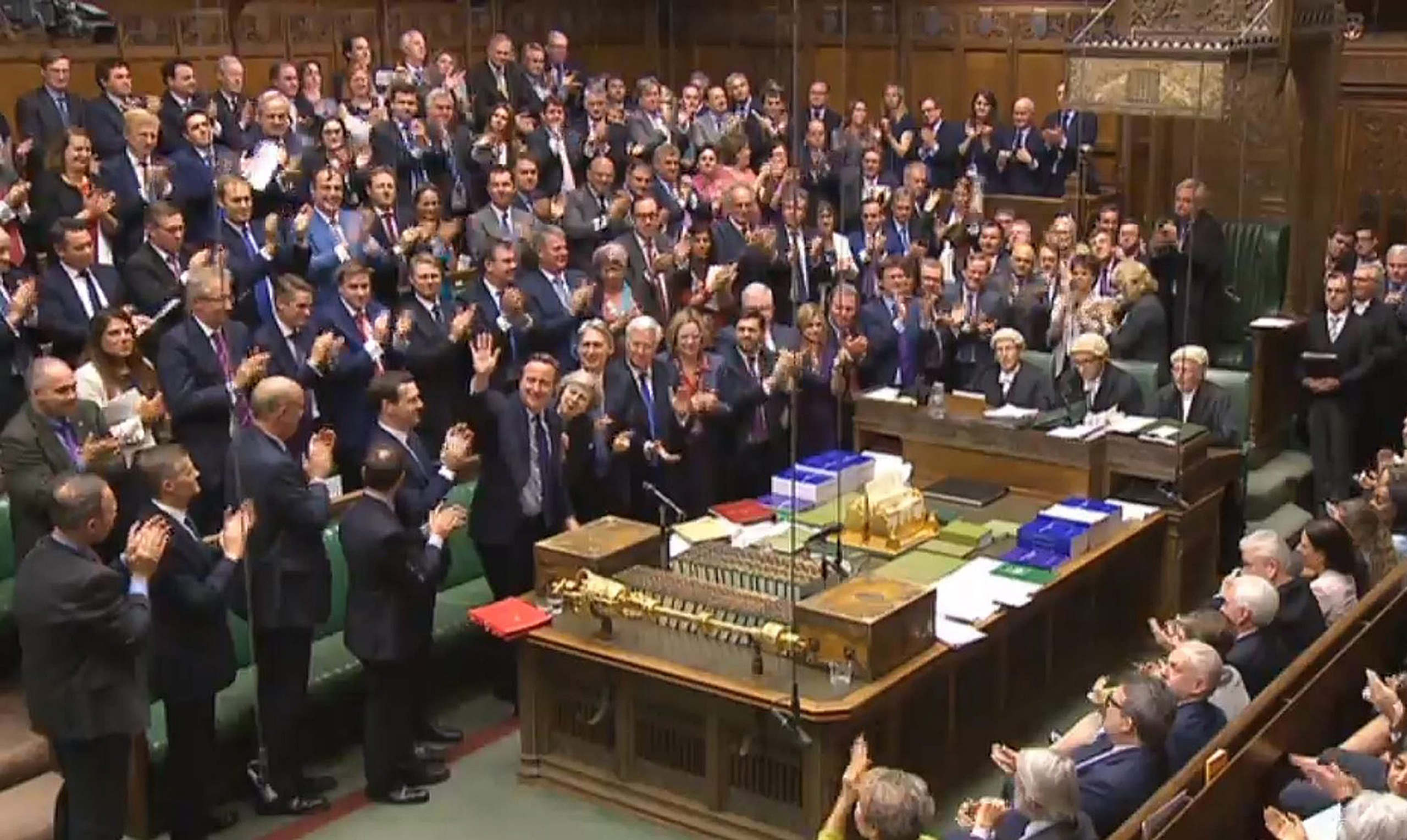 A British Parliament handout photo released shows Conservative Members of Parliament giving outgoing Prime Minister David Cameron a standing ovation after finishing his last Prime Minister's Questions in the House of Commons, in London on July 13, 2016.
