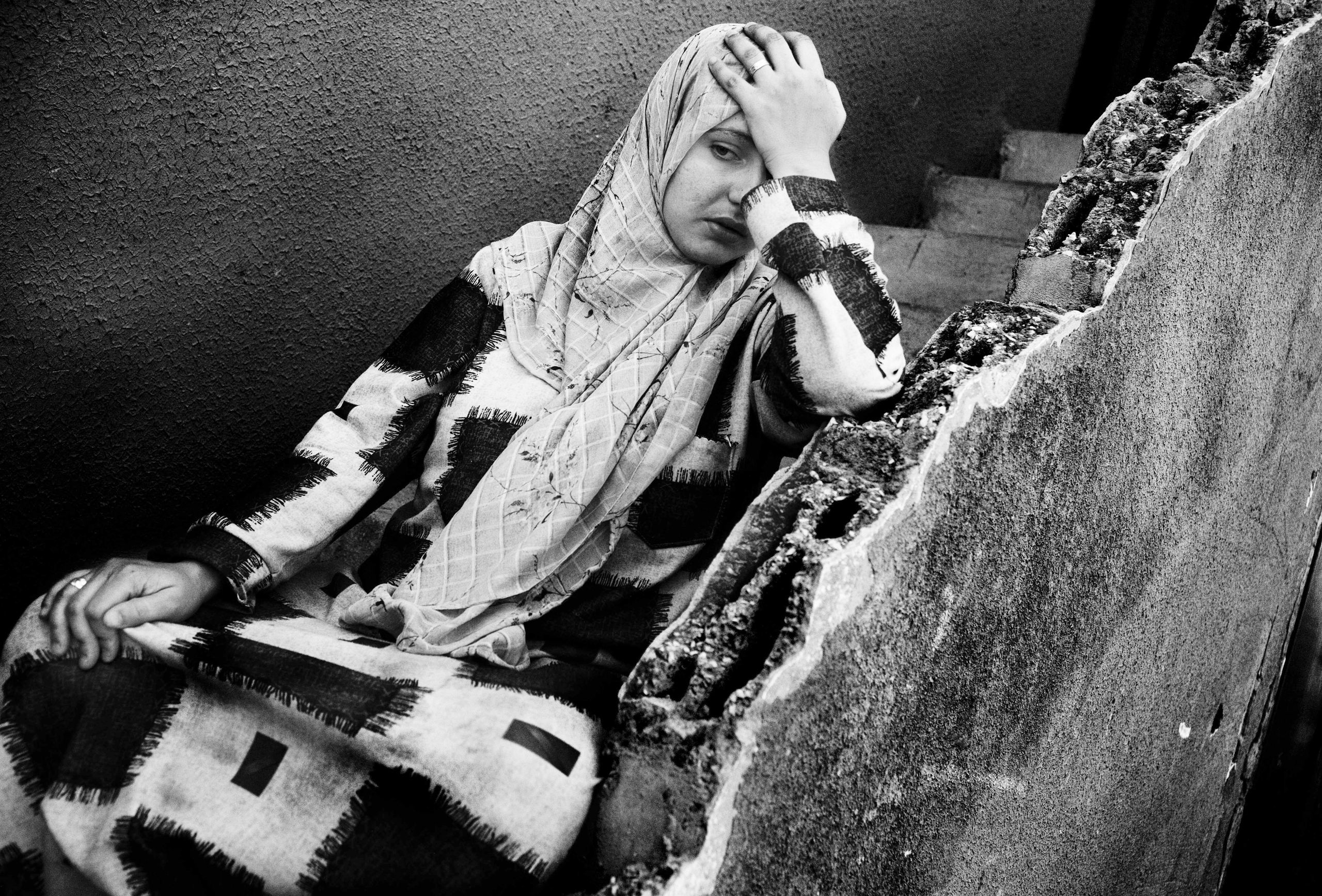 A woman desperate to flee the village is sitting on the stairs of her house. Ramesh, Lebanon, July 2006.