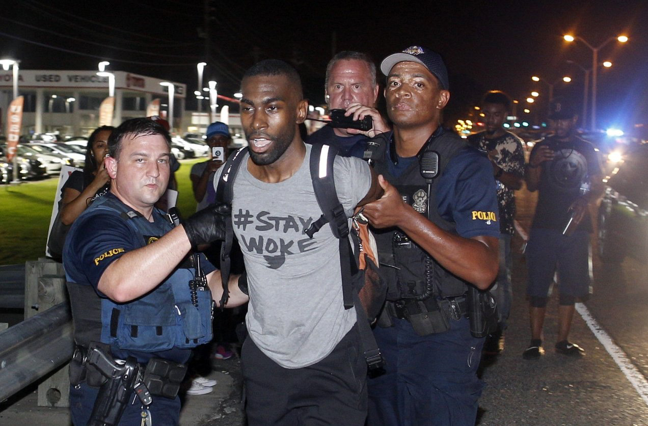 Police arrest activist DeRay McKesson during a protest along Airline Highway, a major road that passes in front of the Baton Rouge Police Department headquarters, July 9, 2016.