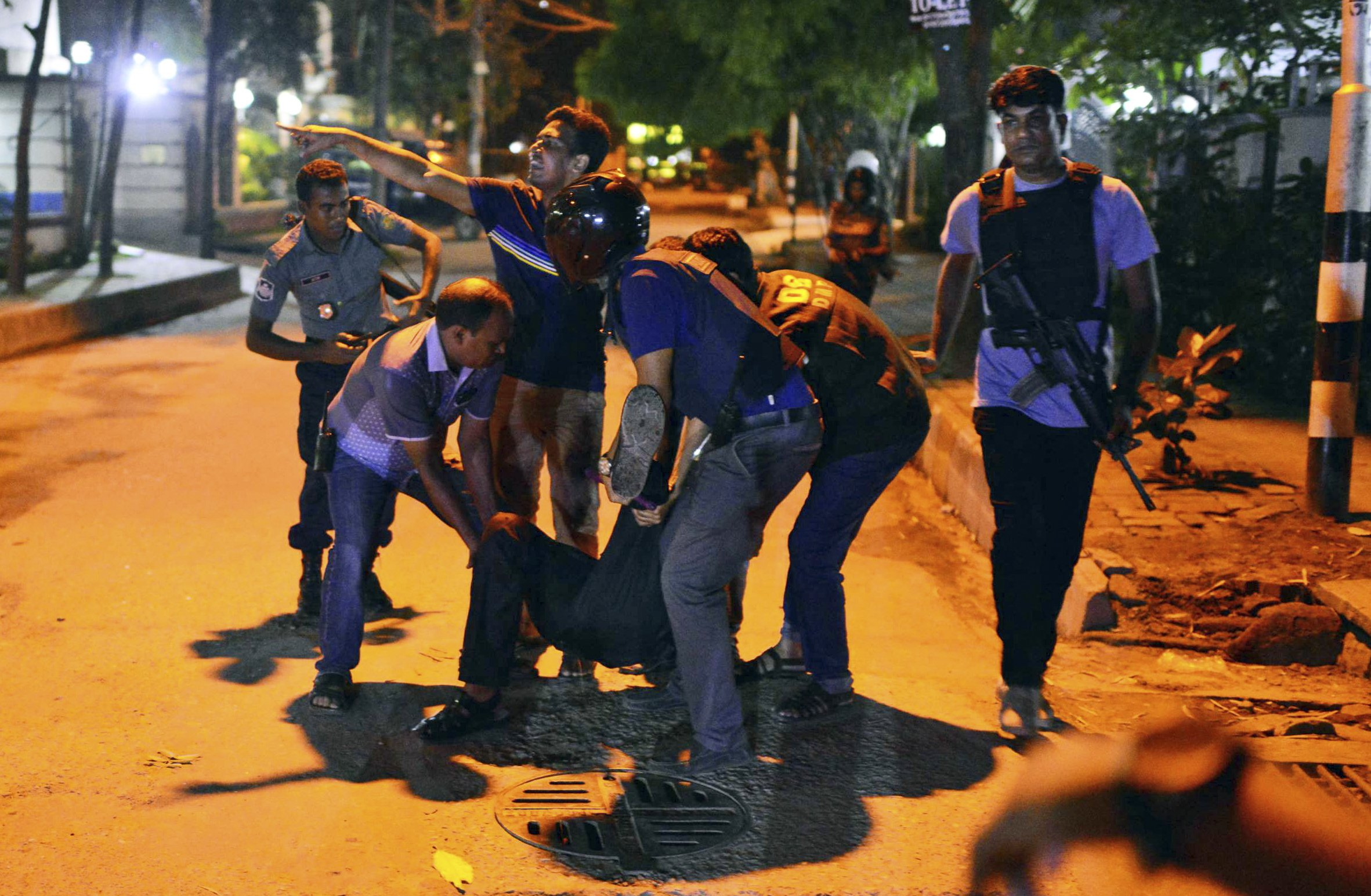 People help an unidentified injured person after a group of gunmen attacked a restaurant popular with foreigners in a diplomatic zone of the Bangladeshi capital of Dhaka on July 1, 2016.