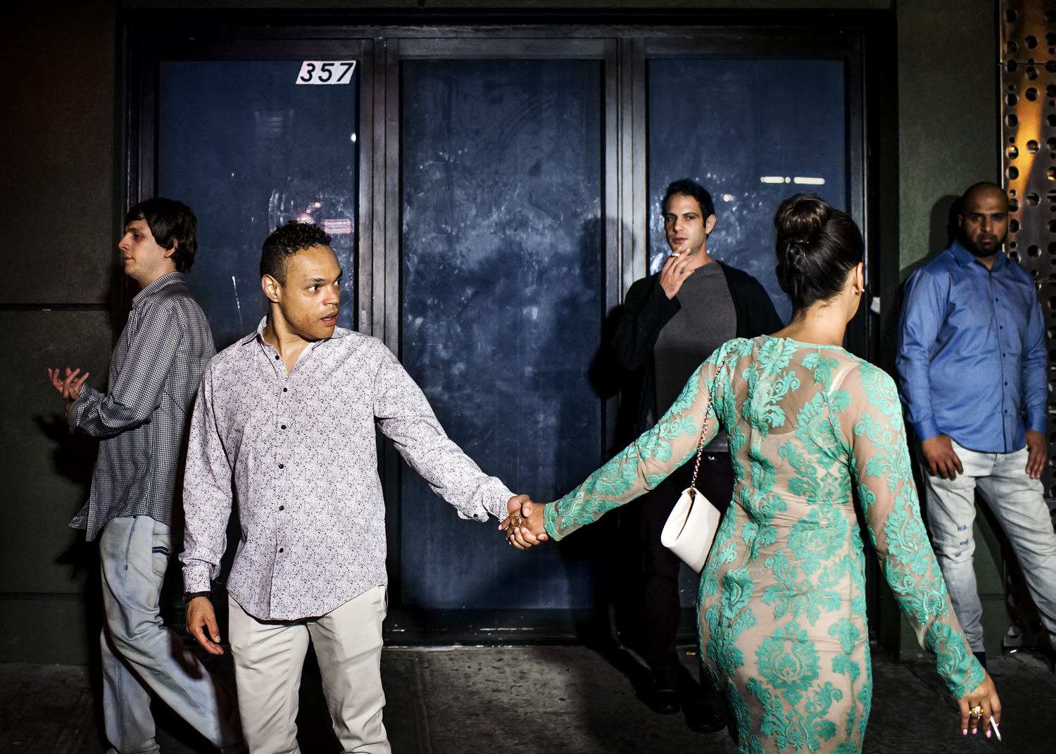 A man grabs a passing woman by the hand in front of the Dream Hotel in September 2015.
