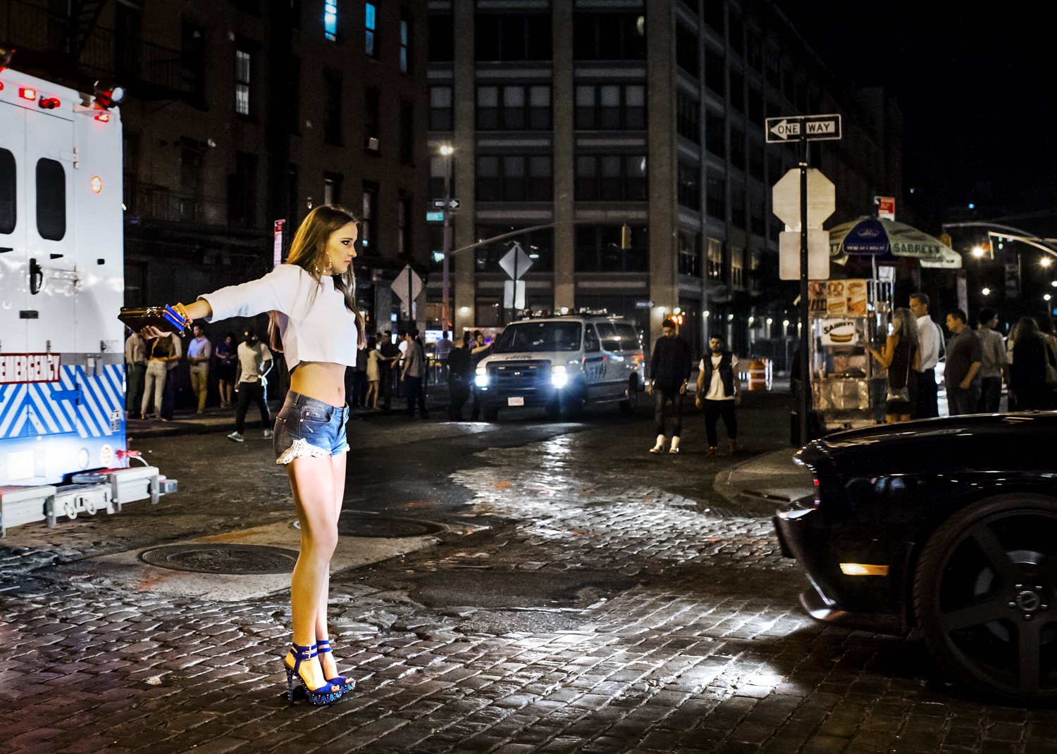 A young woman tries to stop a car at an intersection in the Meatpacking District in June 2014.