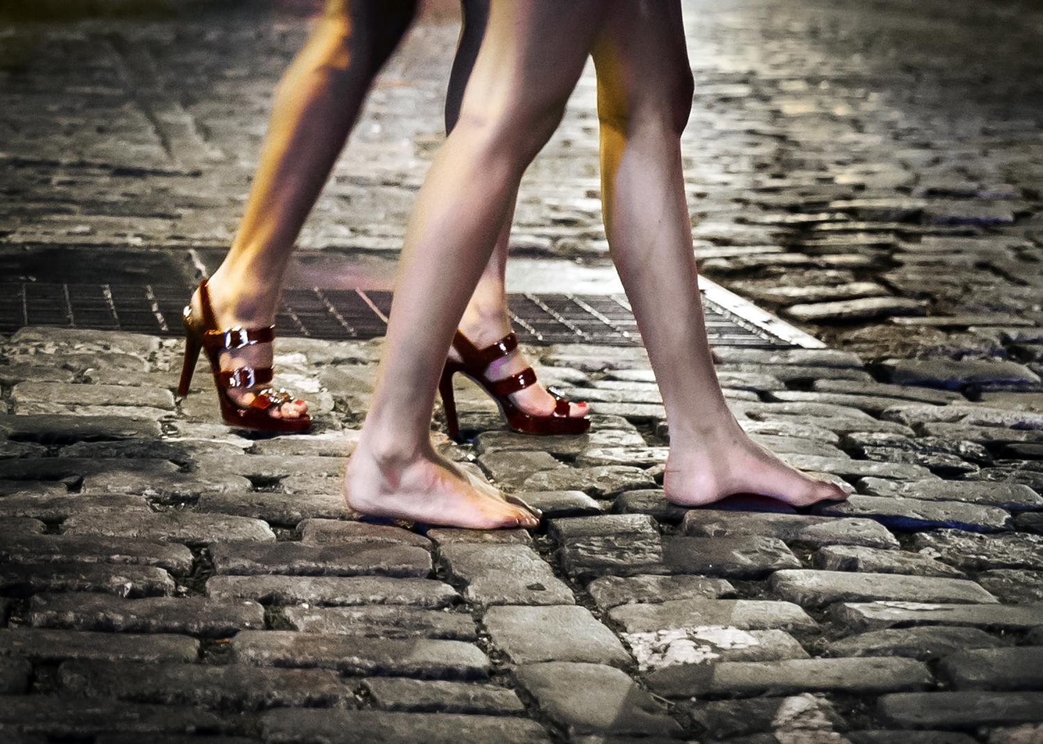 A pair of women walk on the cobblestone in June 2014.