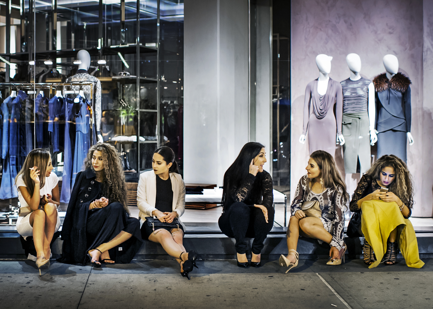 A group of young women sit on the street in the late hours in the Meatpacking District in October 2014.