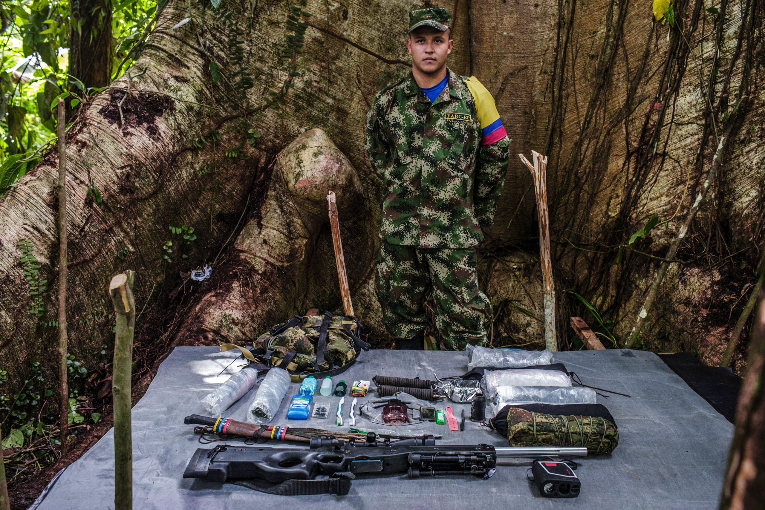 Junior   is a 20-year old, who has been with FARC for seven years.                                He has attended several training courses to learn sniper fire and accuracy for special weapons. He uses tactical binoculars to calculate the distance between the target and the shooter. In order to move through the jungle swiftly, his luggage is lightweight.
