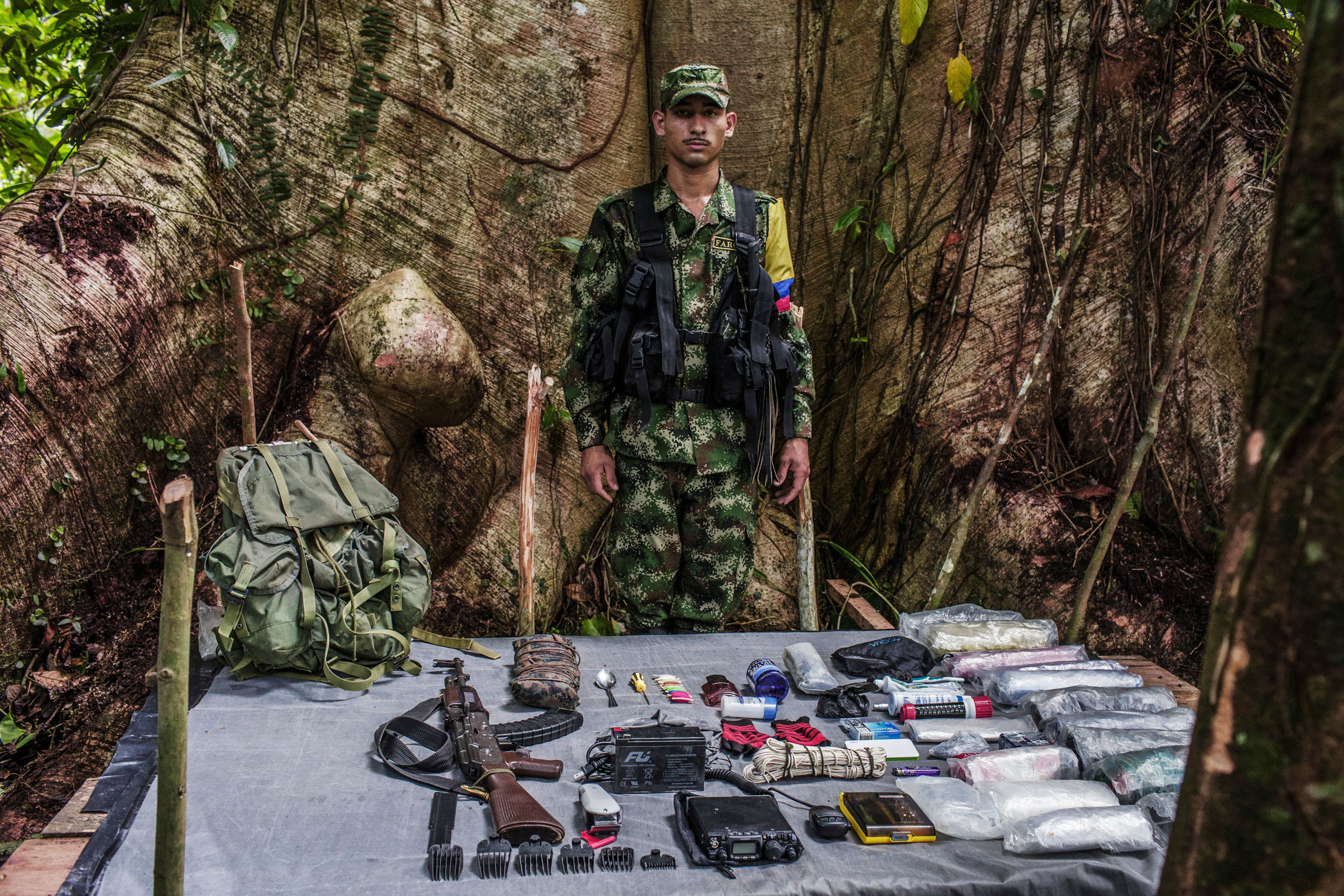 Carlos,  19-years old is a radio operator and electrician with FARC. The radio requires a four pound battery which he carries, along with tools to repair machinery.