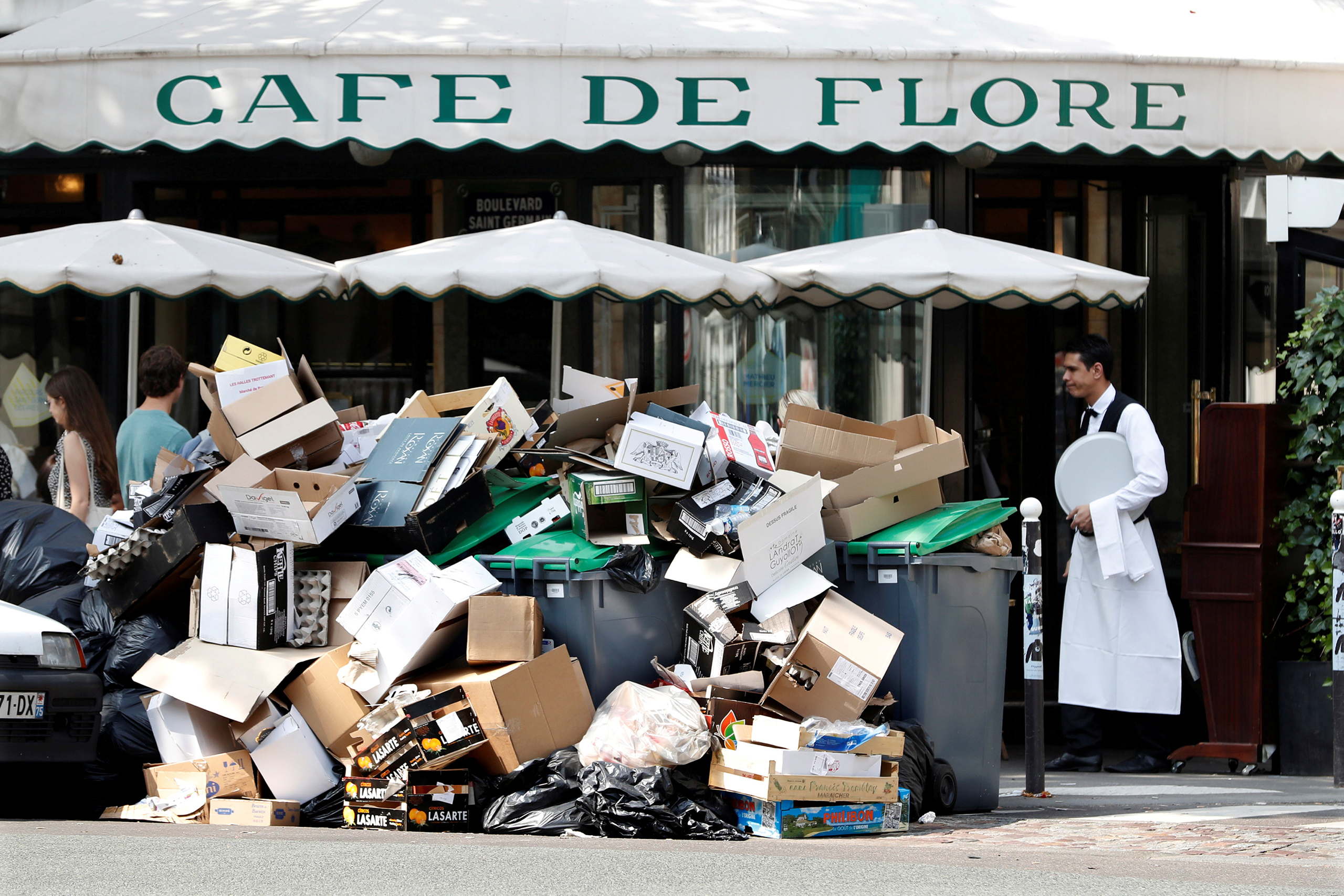 A waiter stands near a pile of garbage bags in front of the Cafe de Flore during a strike of garbage collectors and sewer workers to protest the labour reforms law proposal in Paris on June 8, 2016.