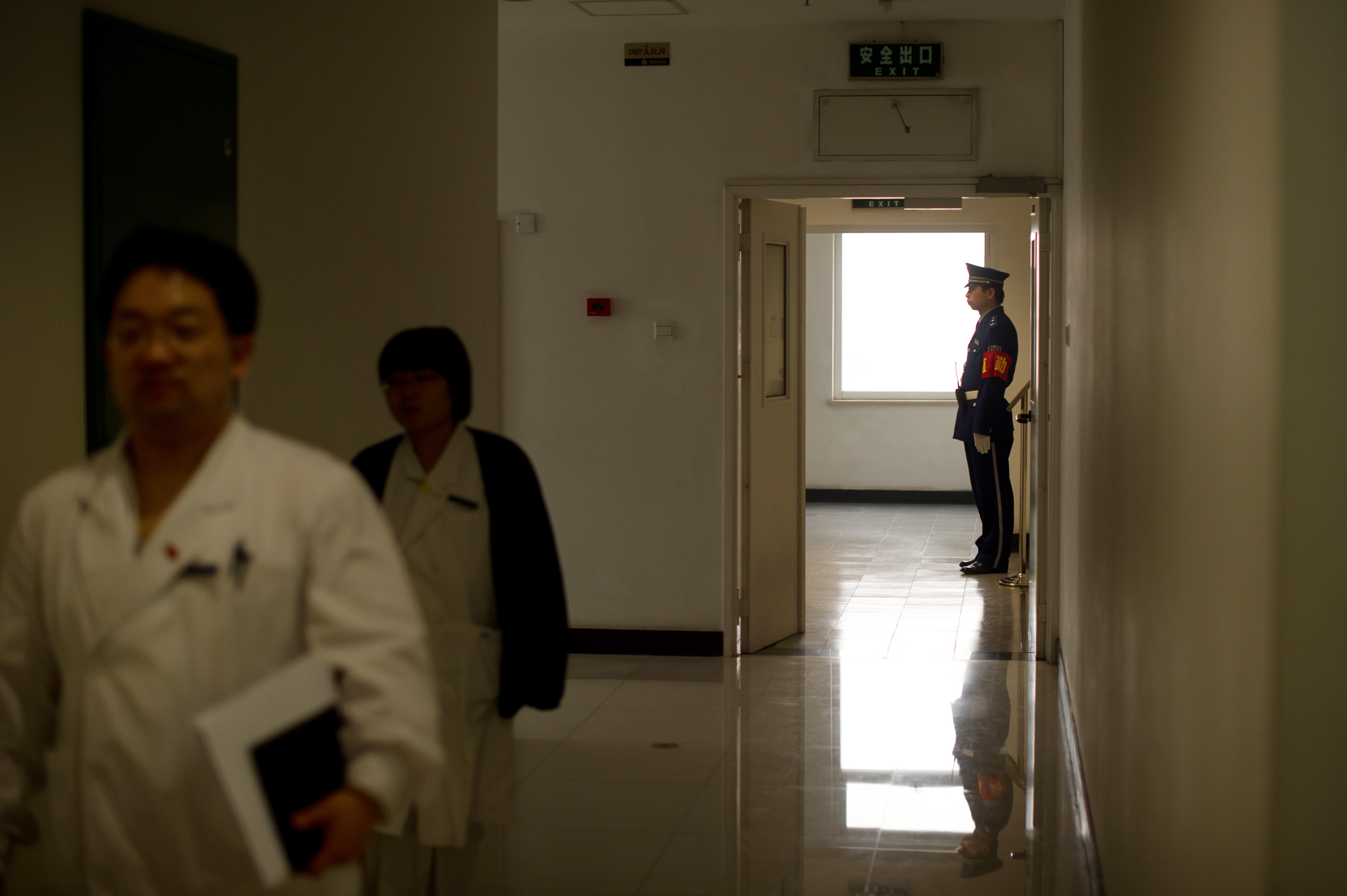 In this file photo, hospital staff walk past a security guard on duty in a hallway at the Beijing Friendship Hospital during a government supervised media tour on February 29, 2012.