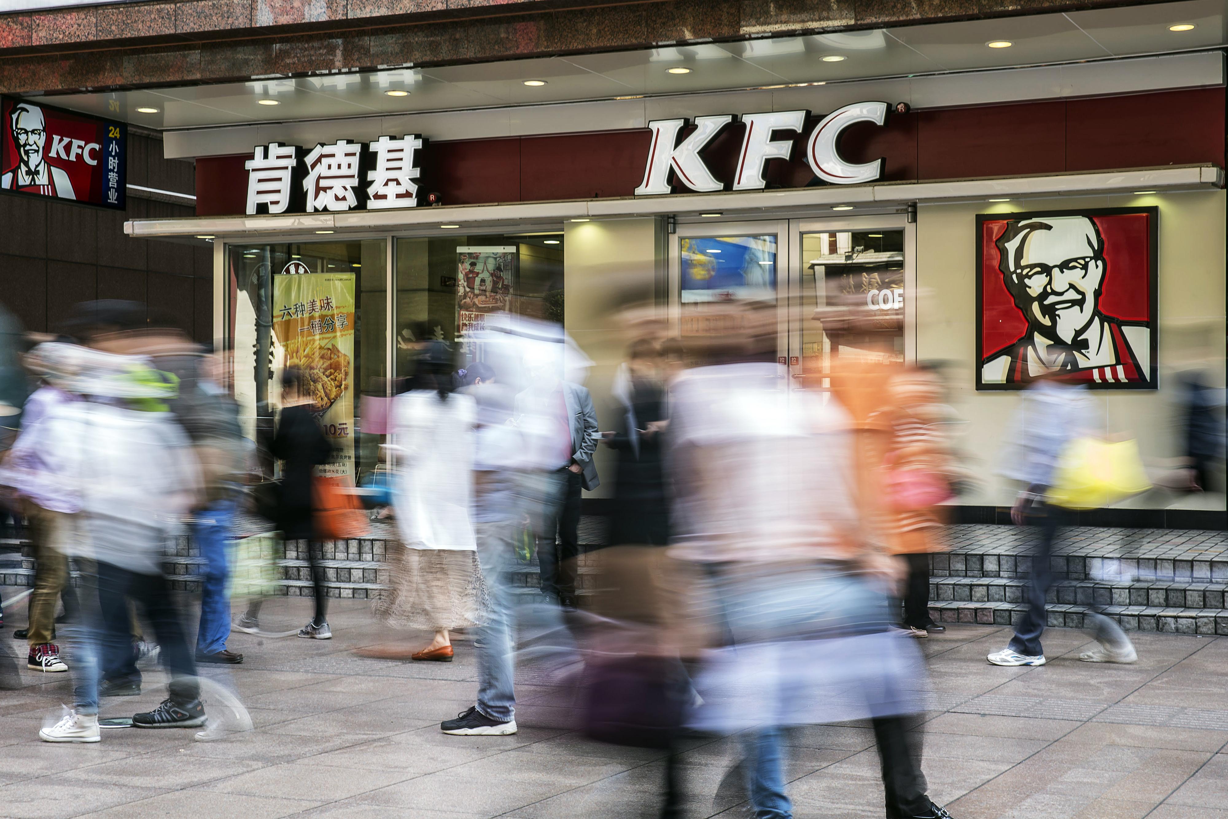 Pedestrians walk past a KFC restaurant in Shanghai, China, on Wednesday, Oct. 21, 2015.