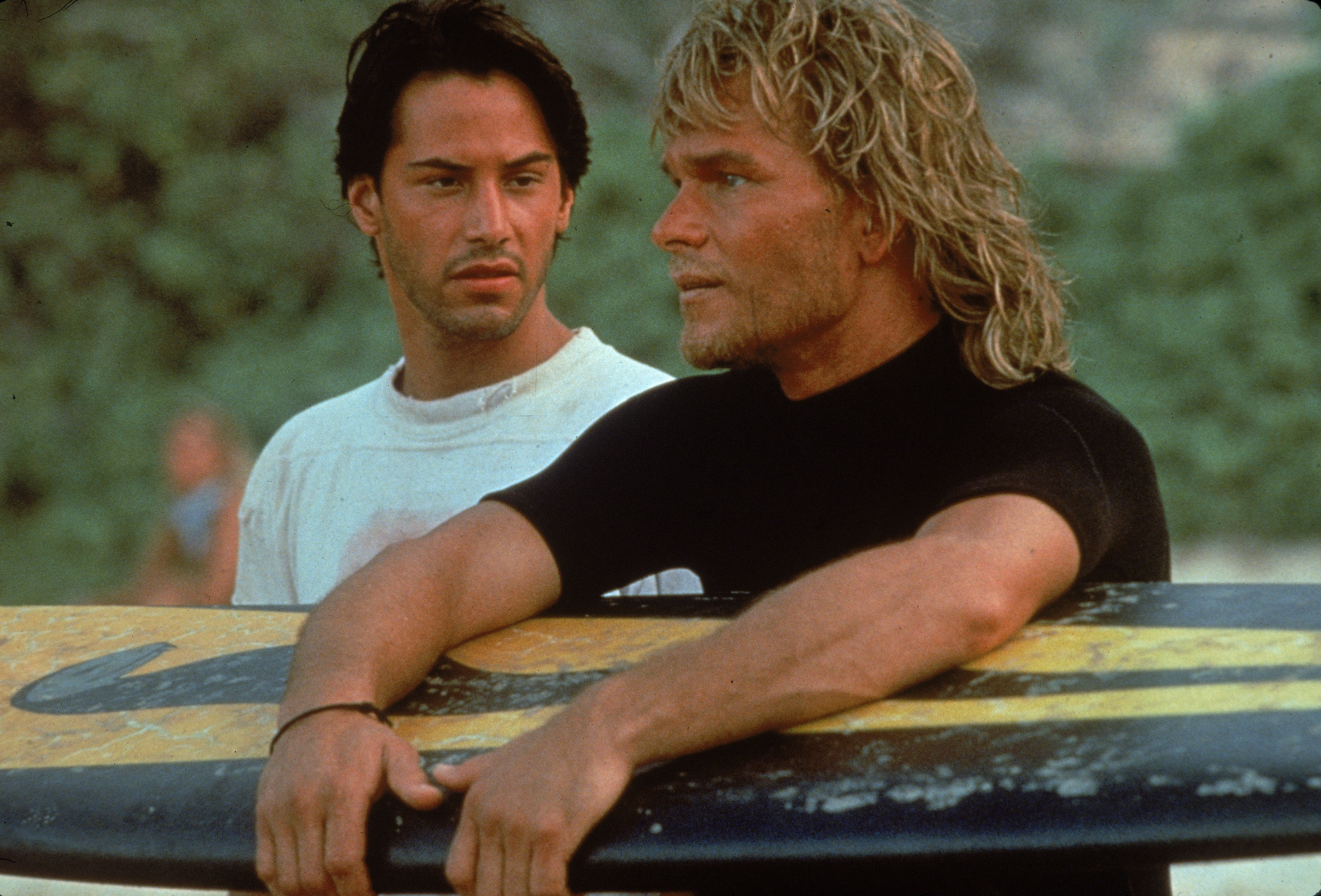 Lebanese-born American actor Keanu Reeves and American actor Patrick Swayze stand on a beach as Swayze holds a surfboard during the filming of the action movie Point Break directed by Kathryn Bigelow, 1991.