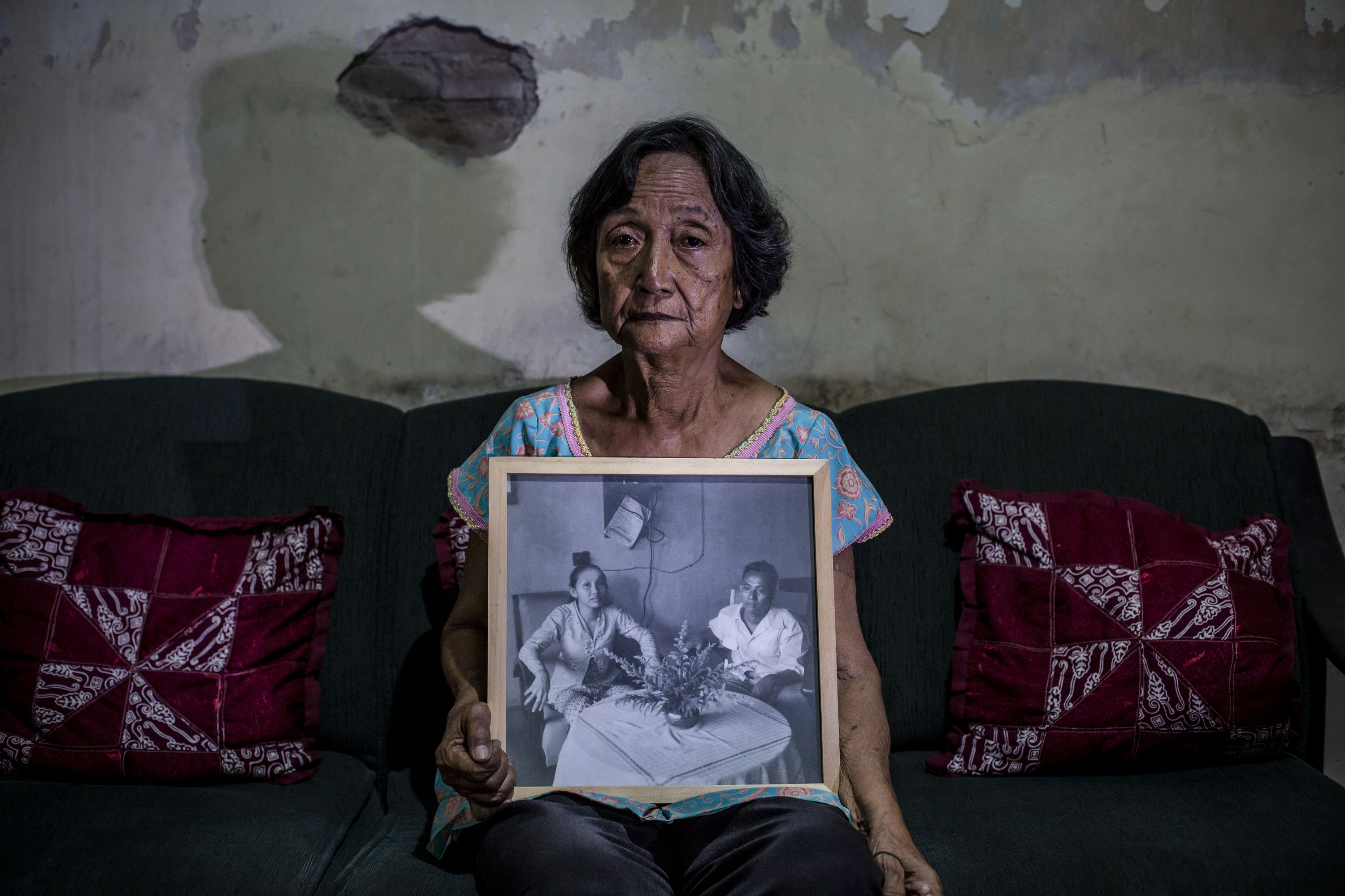Sri Muhayati, 75, holds a photograph of her parents on May 6, 2016, in Yogyakarta, Indonesia. Sri spent five years imprisoned without trial for suspected ties to the Indonesian Communist Party