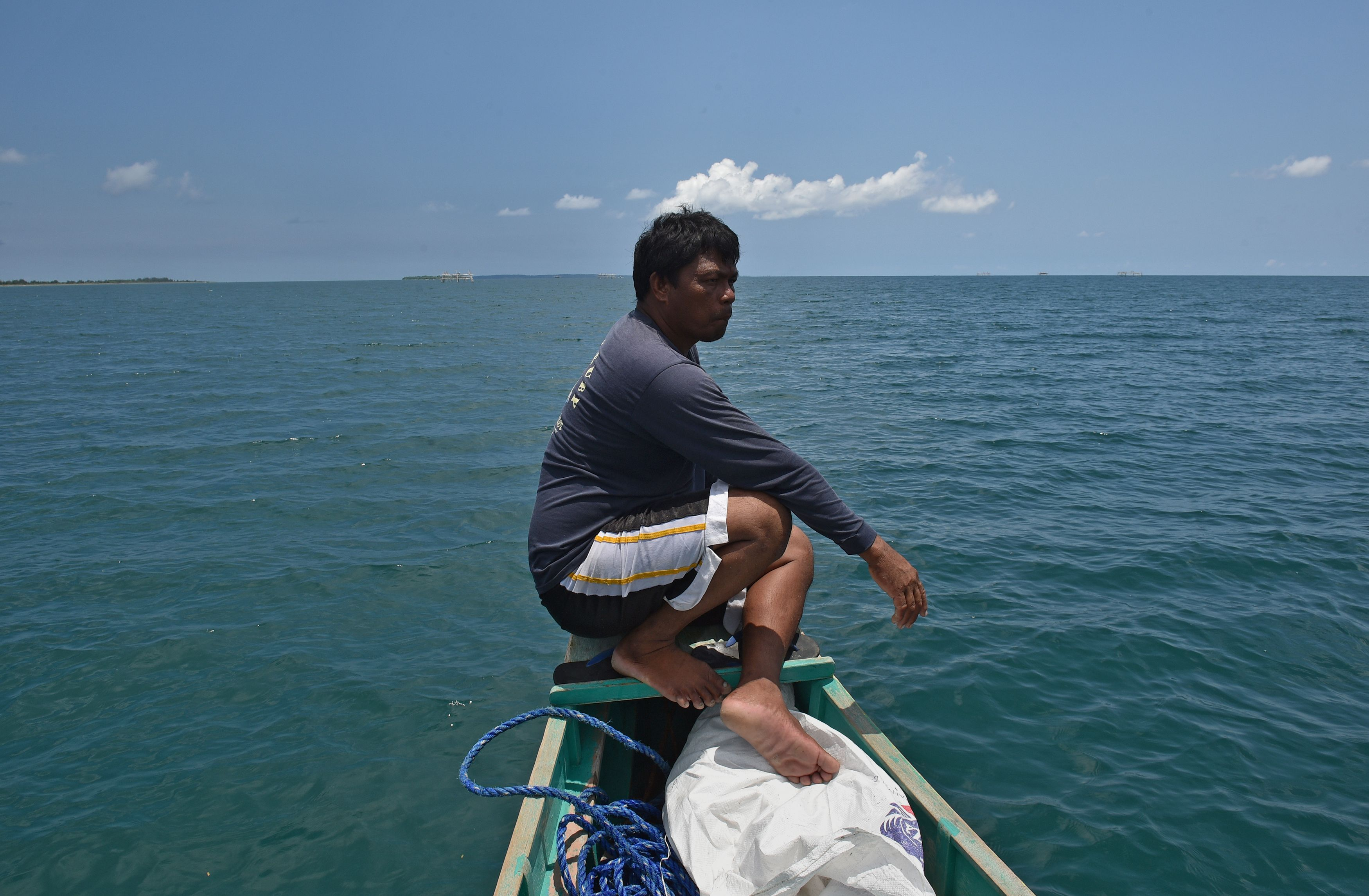 A crew member of a fishing vessel anchored at the mouth of the South China Sea prepares for a fishing expedition to Scarborough Shoal on June 16, 2016.