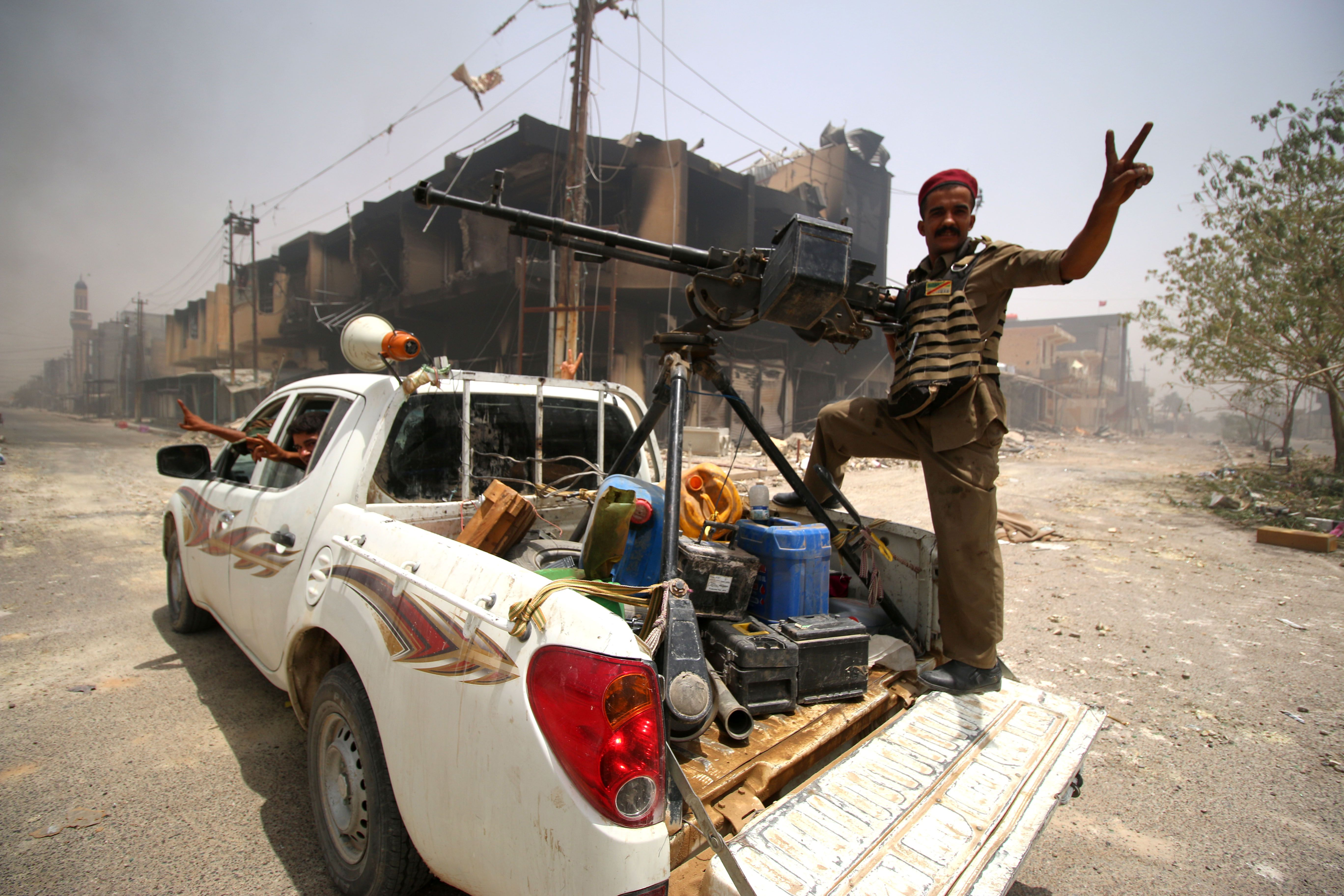 Fighters supporting government forces patrol a street in Fallujah, Iraq, on June 28, 2016, after Iraqi forces retook the city from the Islamic State