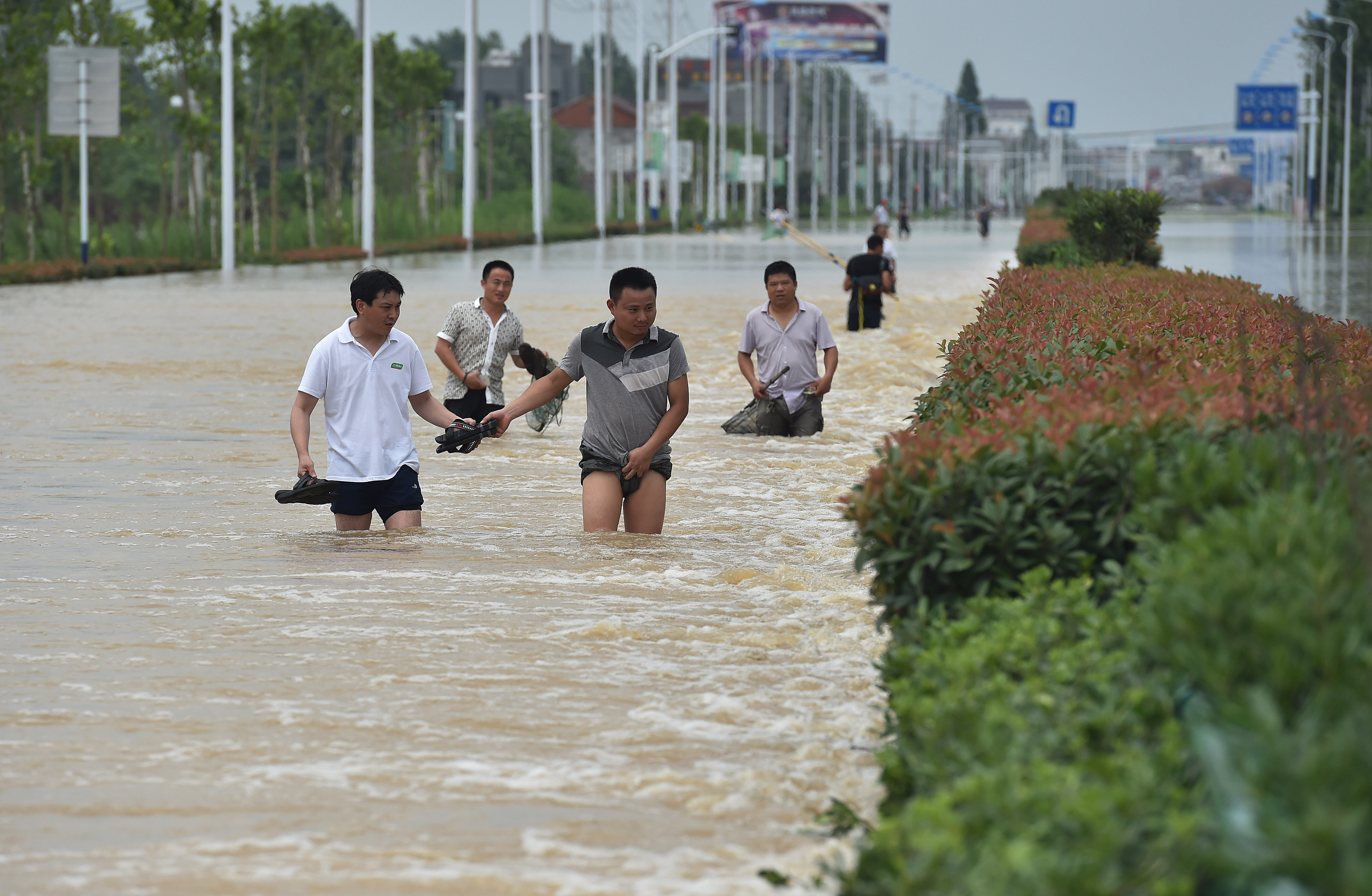 Residents walk in the flood caused by a rainstorm in Shucheng county, China's Anhui province, on July 3, 2016
