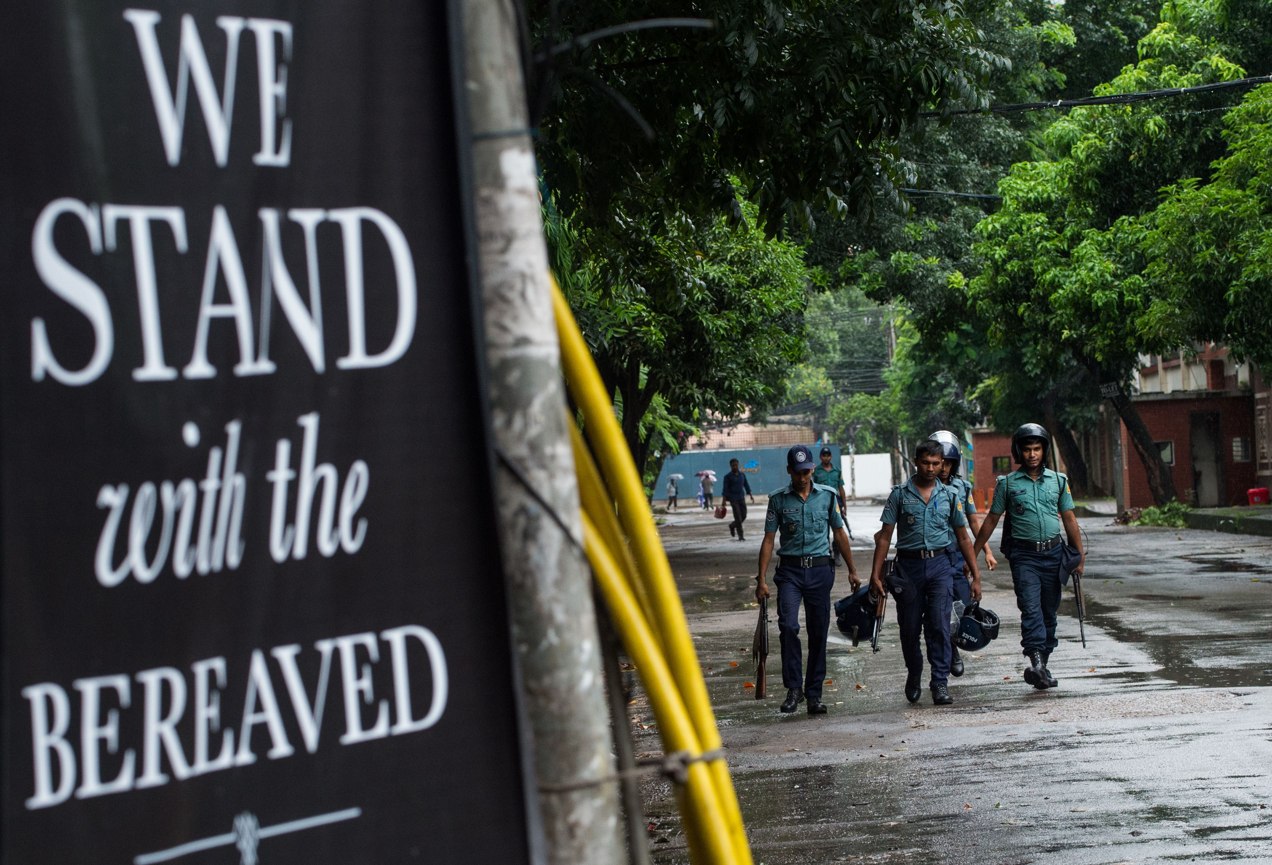 Bangladeshi policemen walk near a banner that reads  We stand with the bereaved  in a street near an upscale restaurant which was the site of a bloody siege that ended in the death of seventeen dead foreigners and five Bangladeshis, including two policemen, in Dhaka on July 5, 2016.