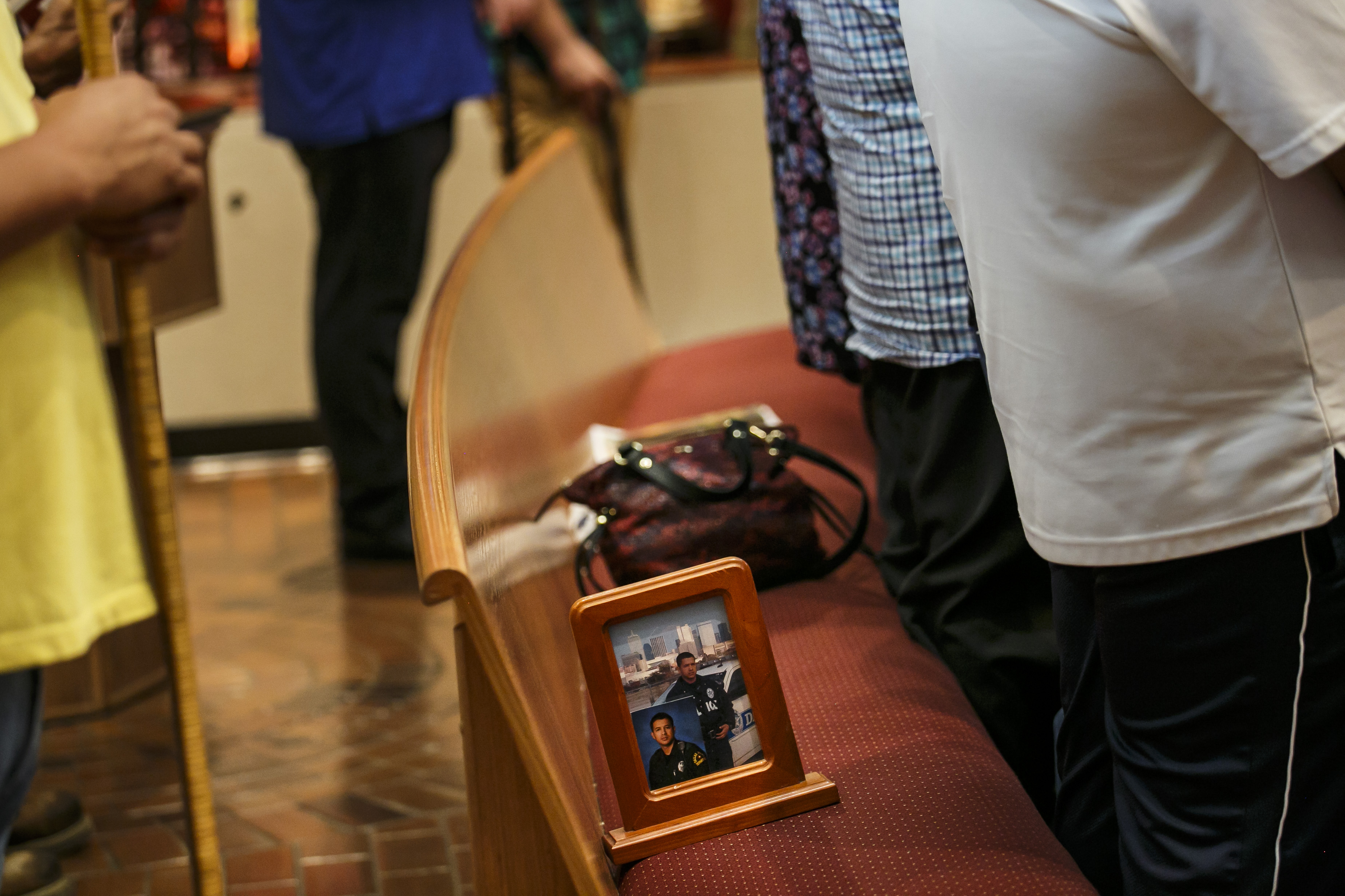 A picture frame with two portraits of slain police officer Patrick Zamarripa, sits on the pew as family members stand to pray during Sunday mass at All Saints Catholic Church, in Dallas, Texas, on July 10, 2016.