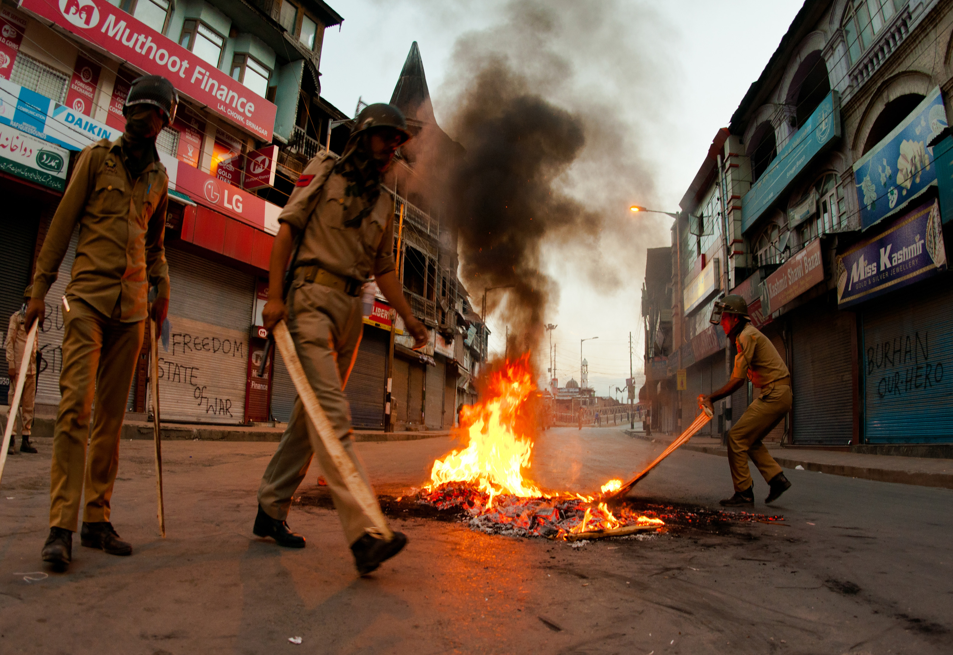 Indian government forces douse a burning tire left by the protesters during a curfew on July 10, 2016, in Srinagar, in the Indian-administered Kashmir, after 21 people were killed and more than 400 injured
