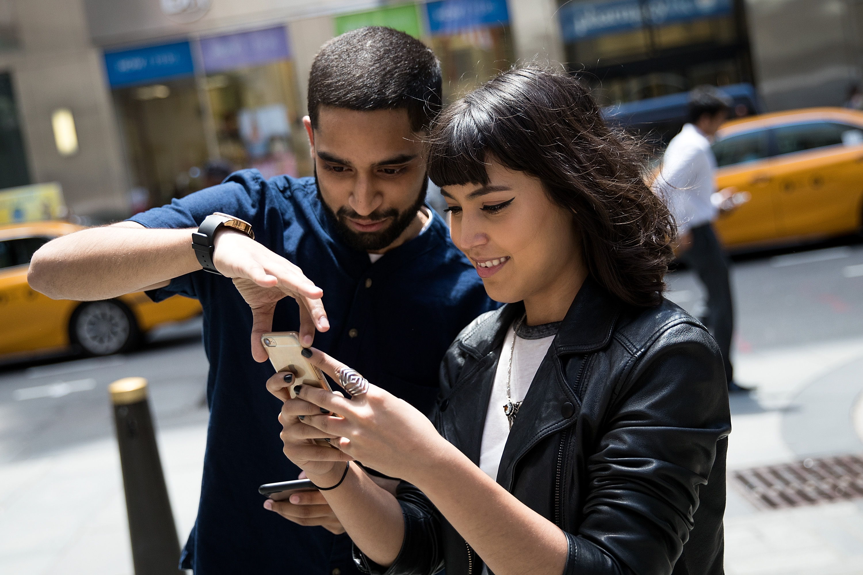 Sameer Uddin and Michelle Macias play Pokemon Go on their smartphones outside of Nintendo's flagship store, July 11, 2016 in New York City.