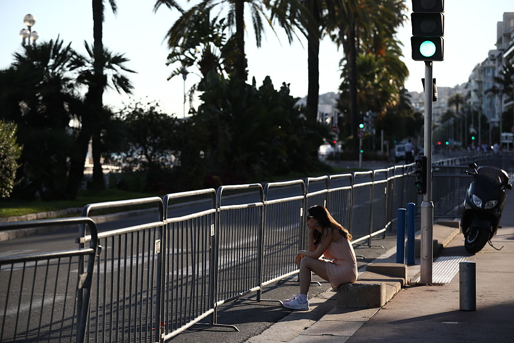 NICE, FRANCE - JULY 15:  A woman sits alone looking pensive towards the Promenade des Anglais on July 15, 2016 in Nice, France. A French-Tunisian attacker killed 84 people as he drove a lorry through crowds, gathered to watch a firework display during Bastille Day Celebrations. The attacker then opened fire on people in the crowd before being shot dead by police.  (Photo by Carl Court/Getty Images)