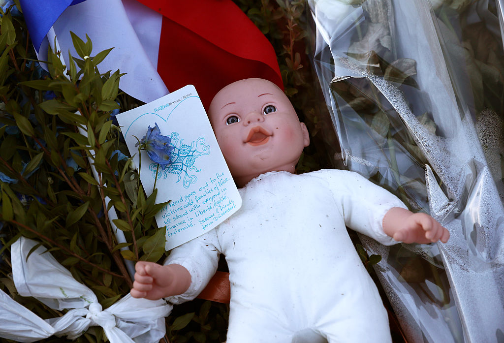 NICE, FRANCE - JULY 15:   A childs doll sits next to a French flag and tributes to the victims of a terror attack on the Promenade des Anglais on July 15, 2016 in Nice, France. A French-Tunisian attacker killed 84 people as he drove a lorry through crowds, gathered to watch a firework display during Bastille Day Celebrations. The attacker then opened fire on people in the crowd before being shot dead by police.  (Photo by Carl Court/Getty Images)
