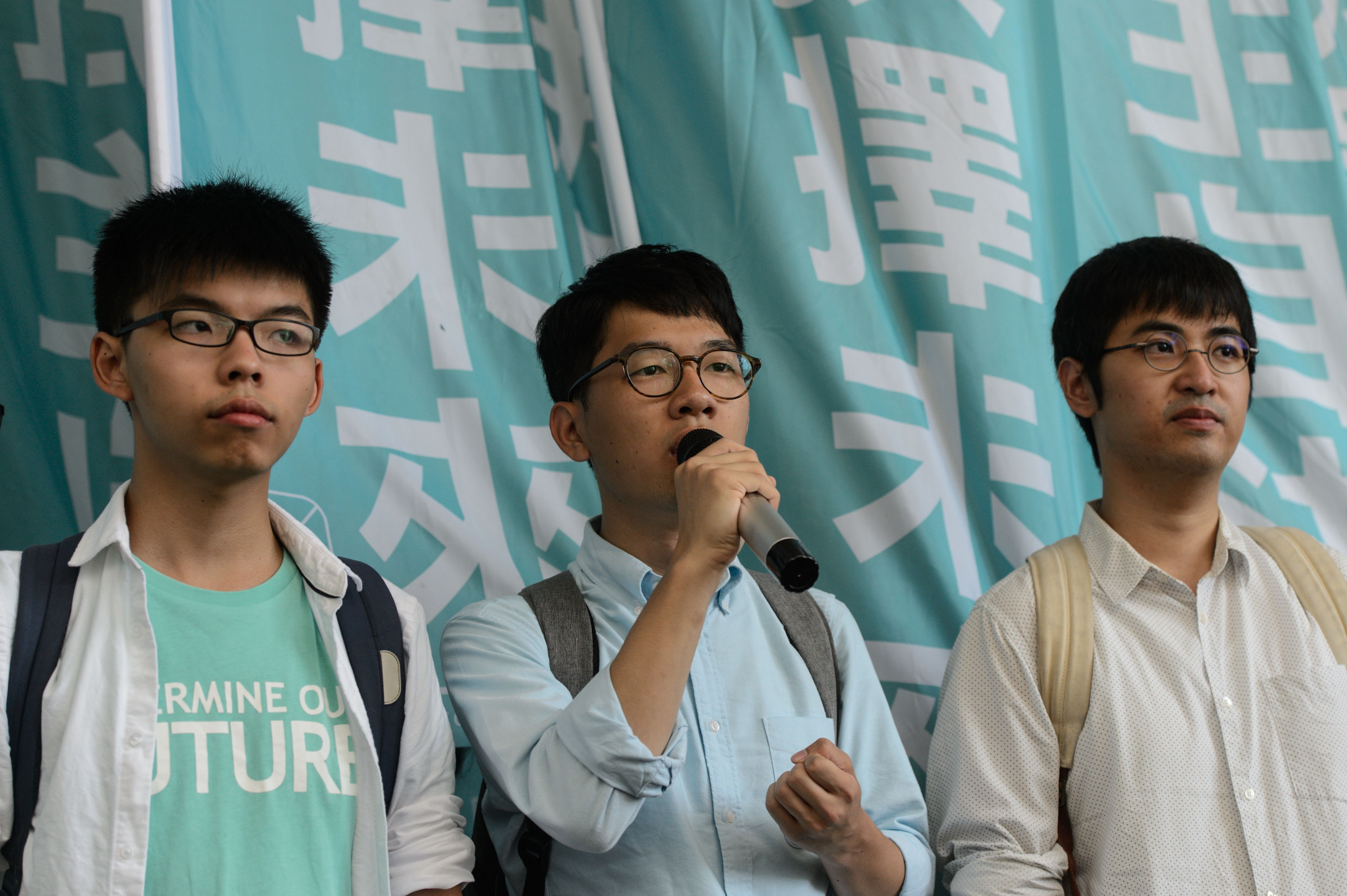 Pro-democracy political activists and members of the Demosistō party, from left, Joshua Wong, Nathan Law and Alex Chow speak as they arrive at the Eastern Magistrates' Court in Hong Kong on July 21, 2016