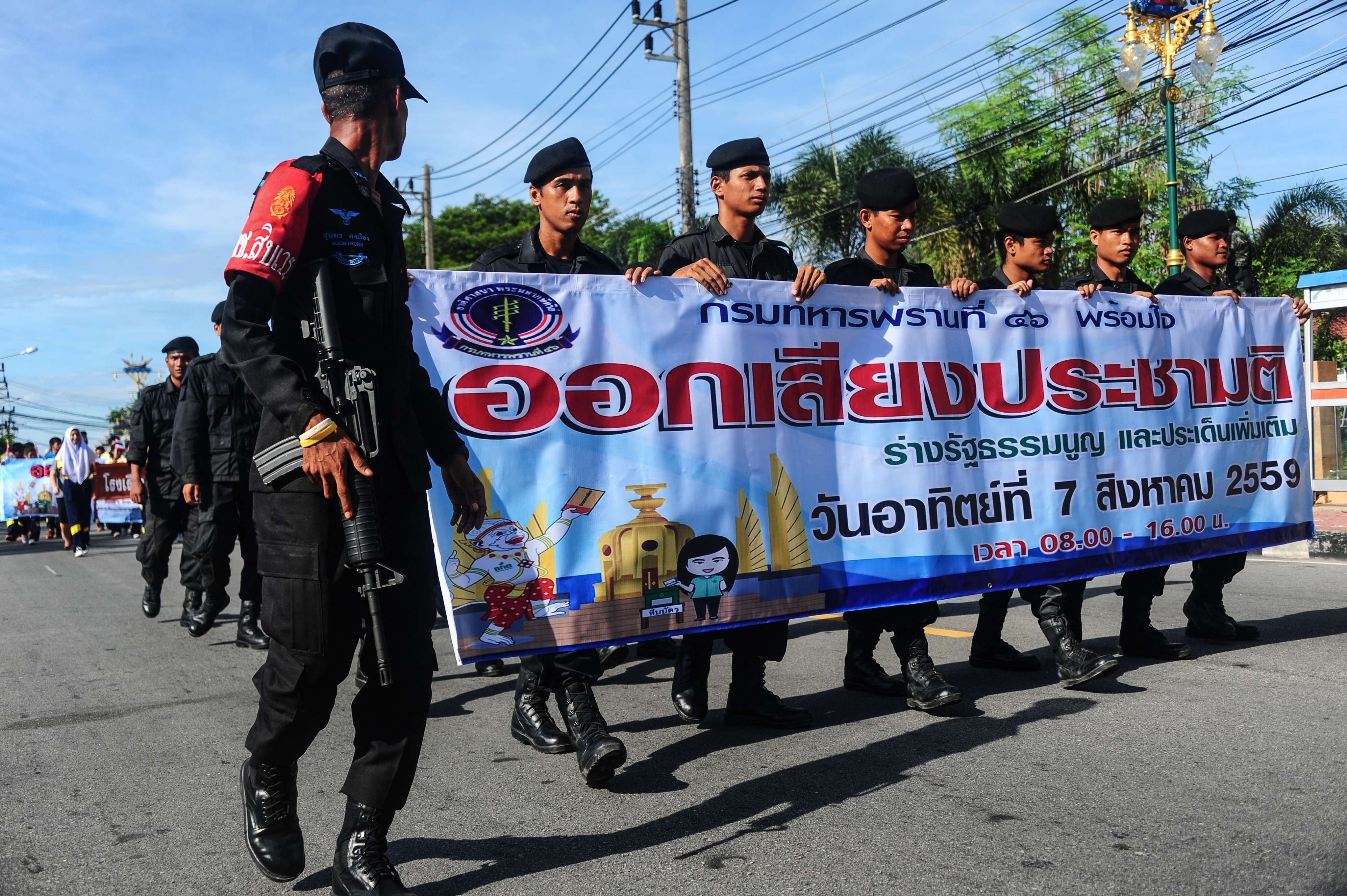 Soldiers hold banners as they march during a campaign encouraging the public to vote in the upcoming referendum on Thailand's draft constitution in Narathiwat province on July 22, 2016.