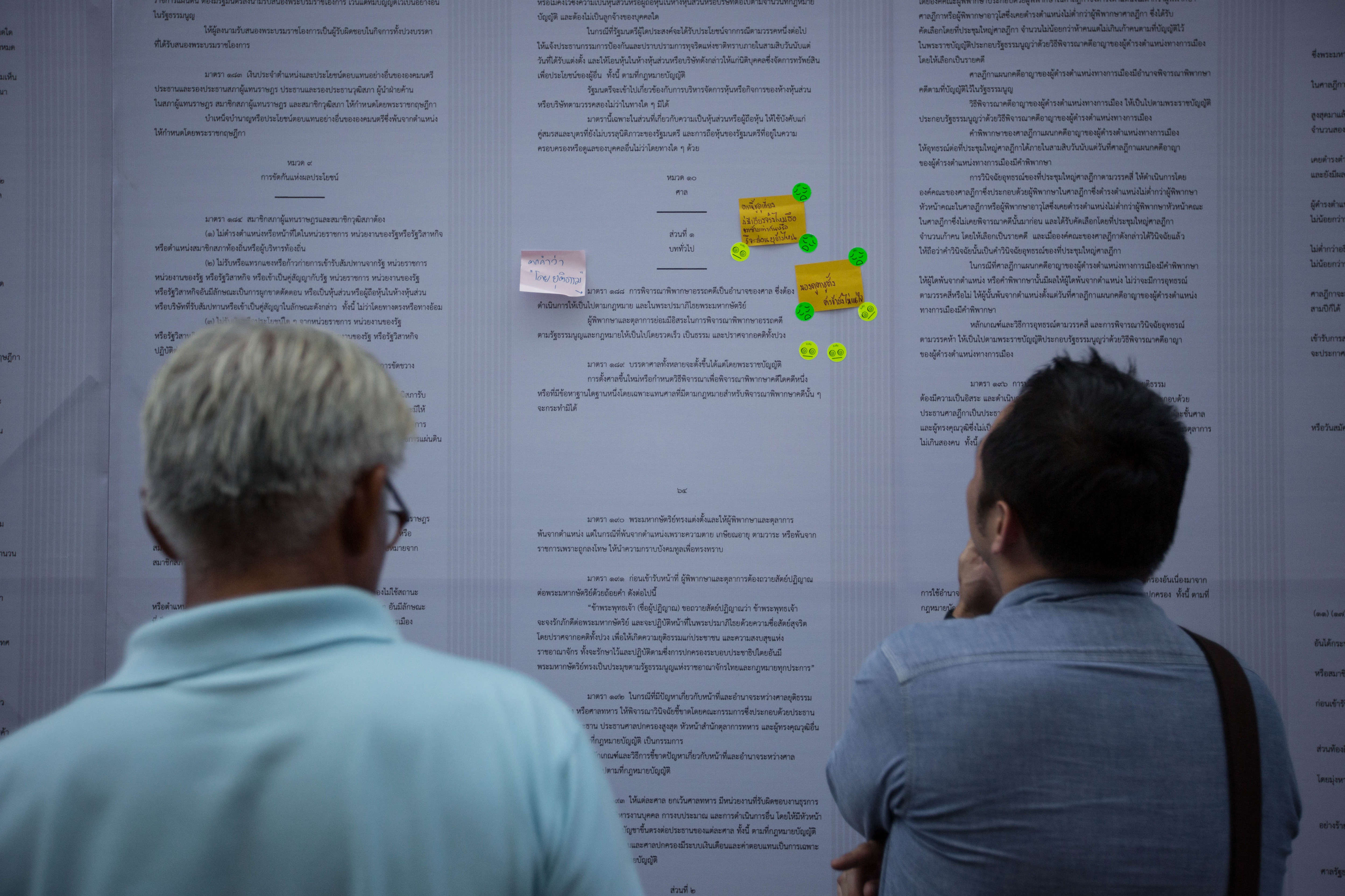 People read the new draft constitution displayed on the wall during the VOTE NO campaign at Thammasat University.