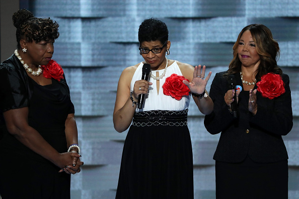 Mothers of the Movement Geneva Reed-Veal (C), mother of Sandra Bland delivers remarks as Lucia McBath (R), mother of Jordan Davis; and Gwen Carr, mother of Eric Garner look on during the second day of the Democratic National Convention at the Wells Fargo Center, July 26, 2016 in Philadelphia, Pennsylvania.