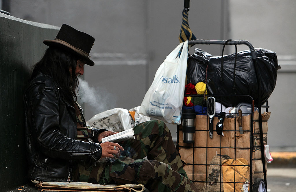 SAN FRANCISCO - JANUARY 25:  A homeless man named Joe reads a book under an overpass where he sleeps January 25, 2010 in San Francisco, California. San Francisco Mayor Gavin Newsom announced ambitious plans during his recent State of the City address to reduce the city's overall homeless population by one third and the street population by one half before being termed out of office in two years. Over 6,500 homeless people live on the streets and in shelters in San Francisco.  (Photo by Justin Sullivan/Getty Images)