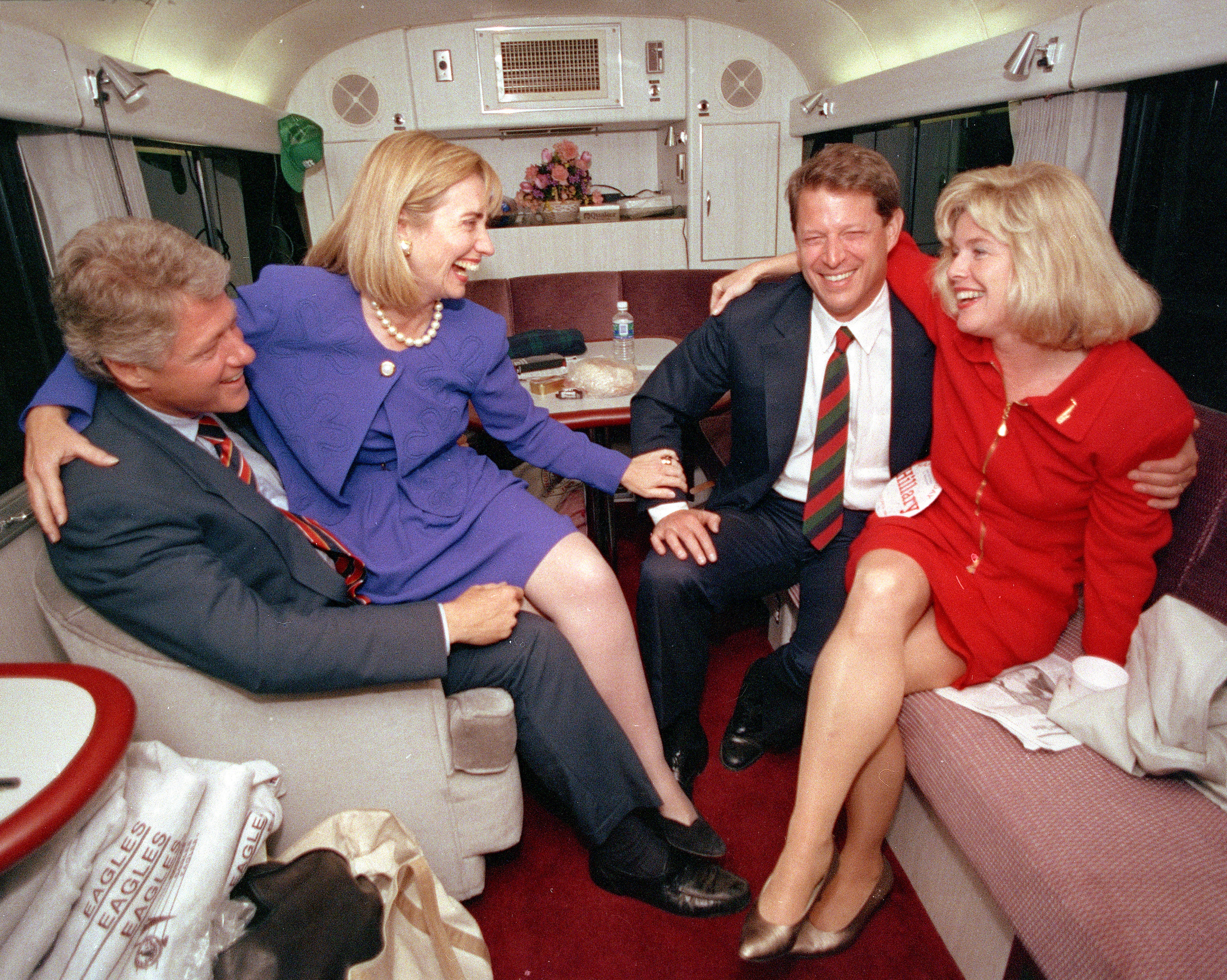 Hillary Rodham Clinton sits on the lap of her husband, democratic presidential candidate Bill Clinton left, as she jokes with vice presidential candidate Al Gore and his wife, Tipper, during a brief rest on their bus in Durham, N.C., on Oct. 26, 1992.