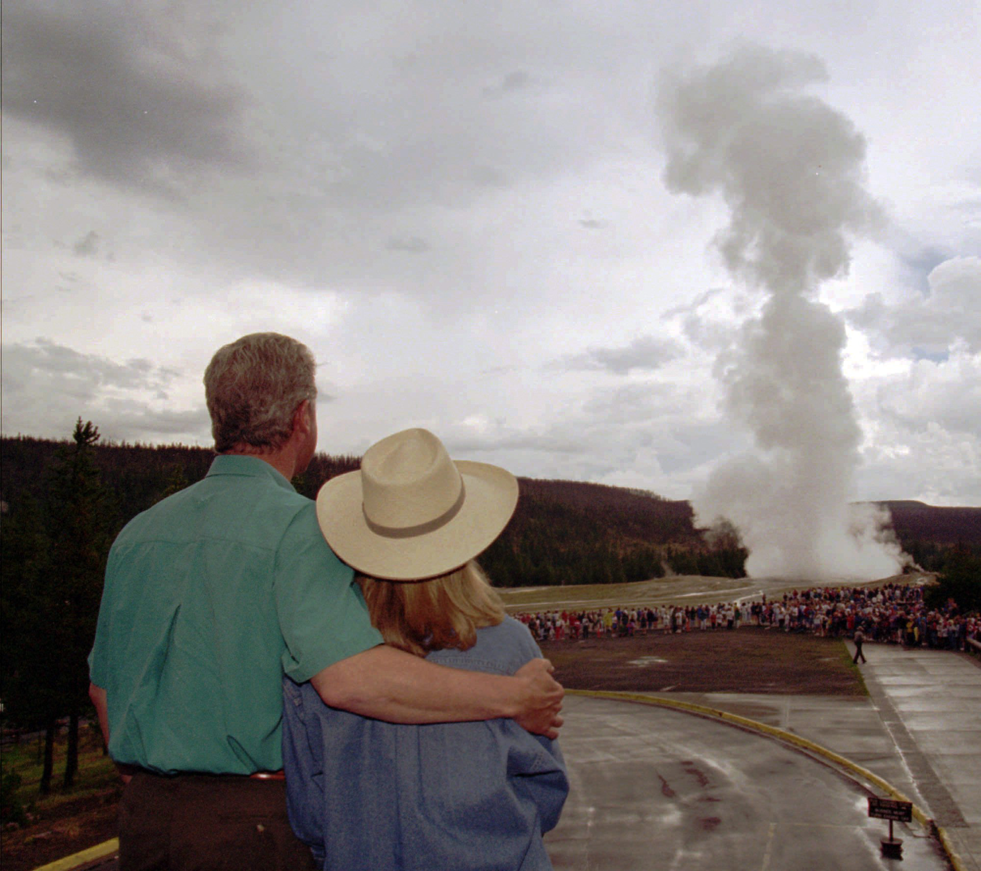 President Bill Clinton puts an arm around his wife, Hillary Clinton, while watching Old Faithful erupt at Yellowstone National Park, Wyo., on Aug. 25, 1995. The first family visited several Yellowstone sites while on vacation.