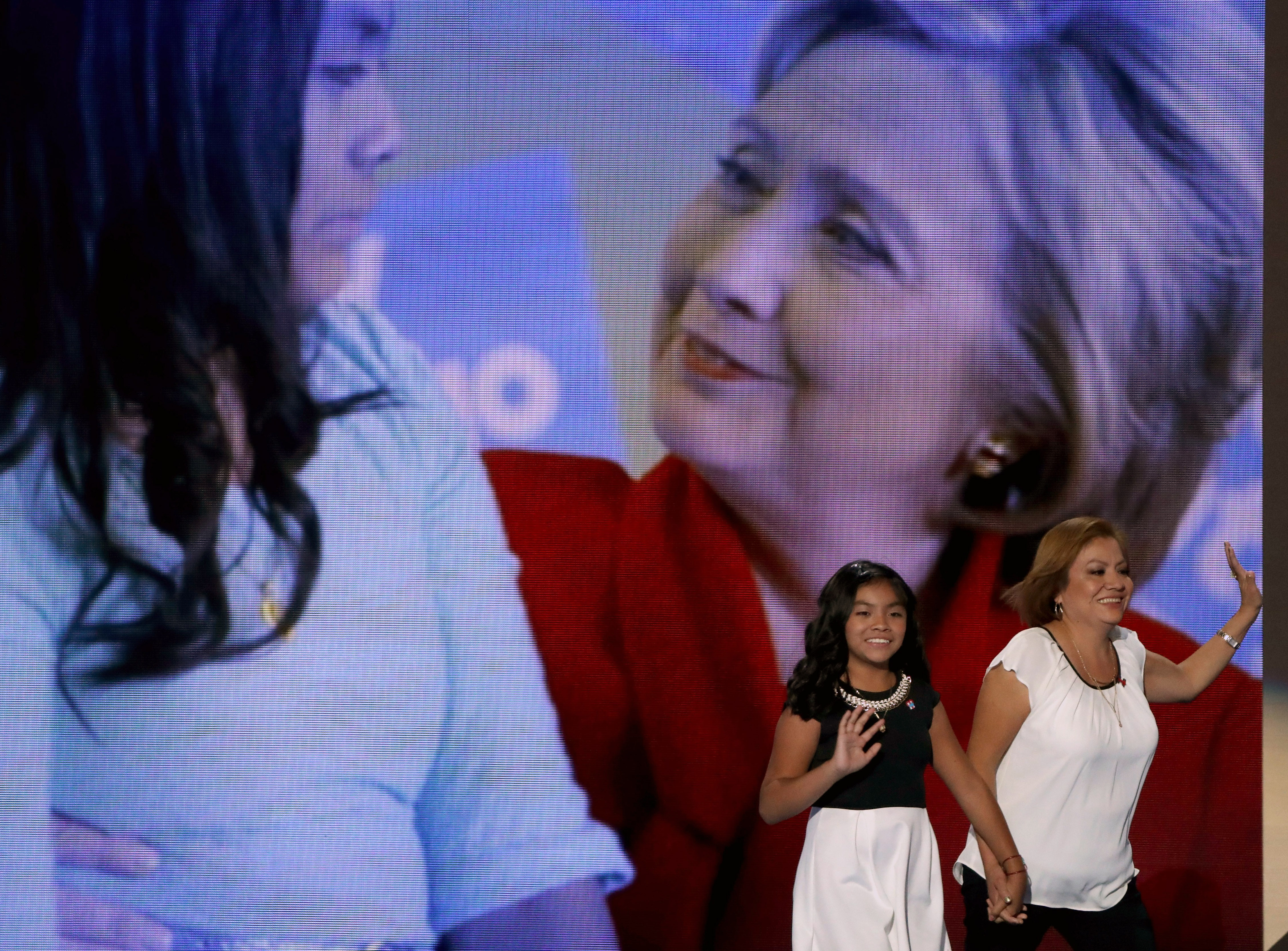 Karla Ortiz, 11, and her mother, Francisca Ortiz, walk out on stage to deliver remarks on the first day of the Democratic National Convention at the Wells Fargo Center, July 25, 2016 in Philadelphia.