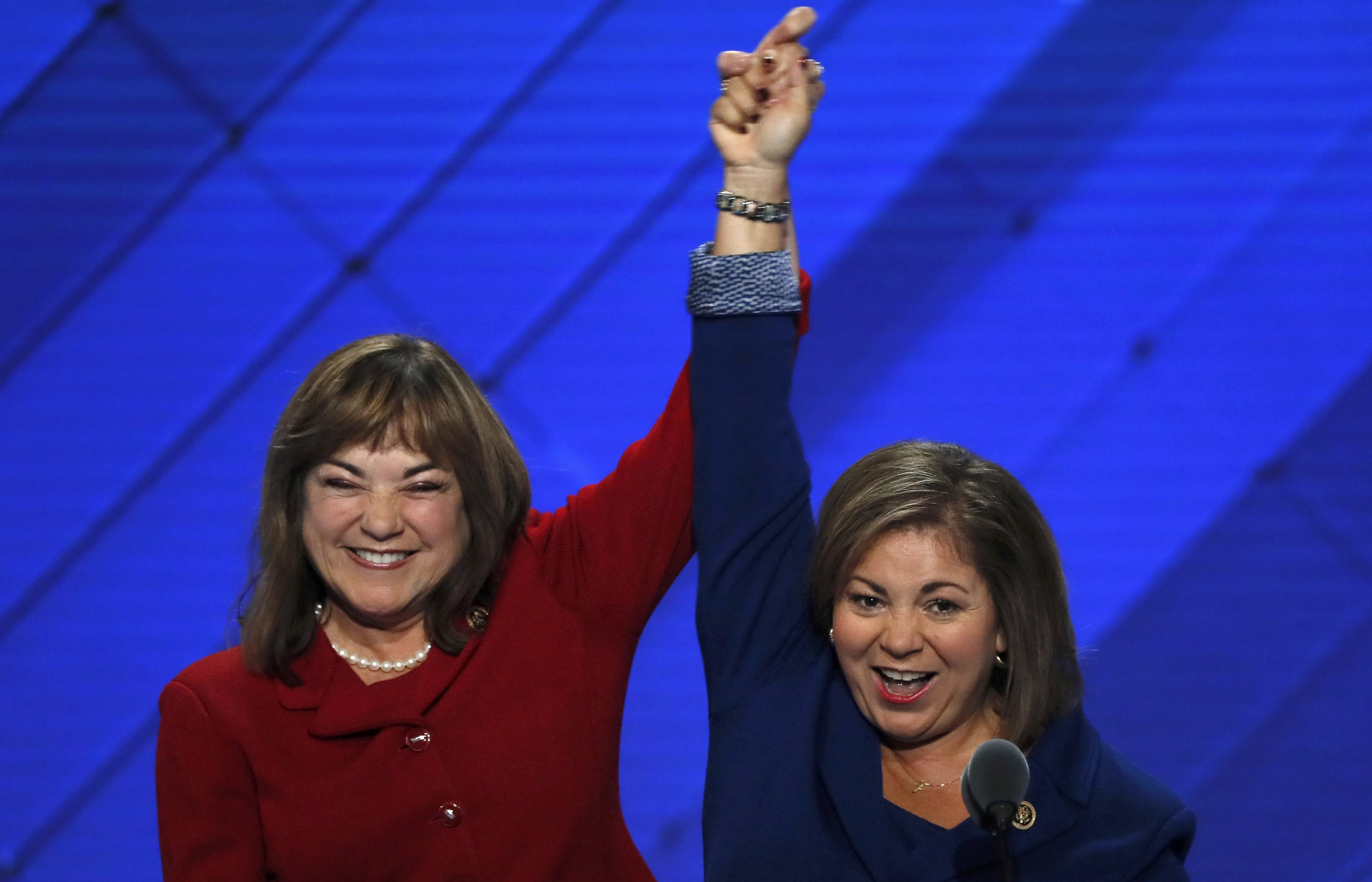 U.S. Rep. Linda Sanchez (D-CA) (R) and her sister and fellow Rep. Loretta join hands onstage at the Democratic National Convention in Philadelphia on July 25, 2016.