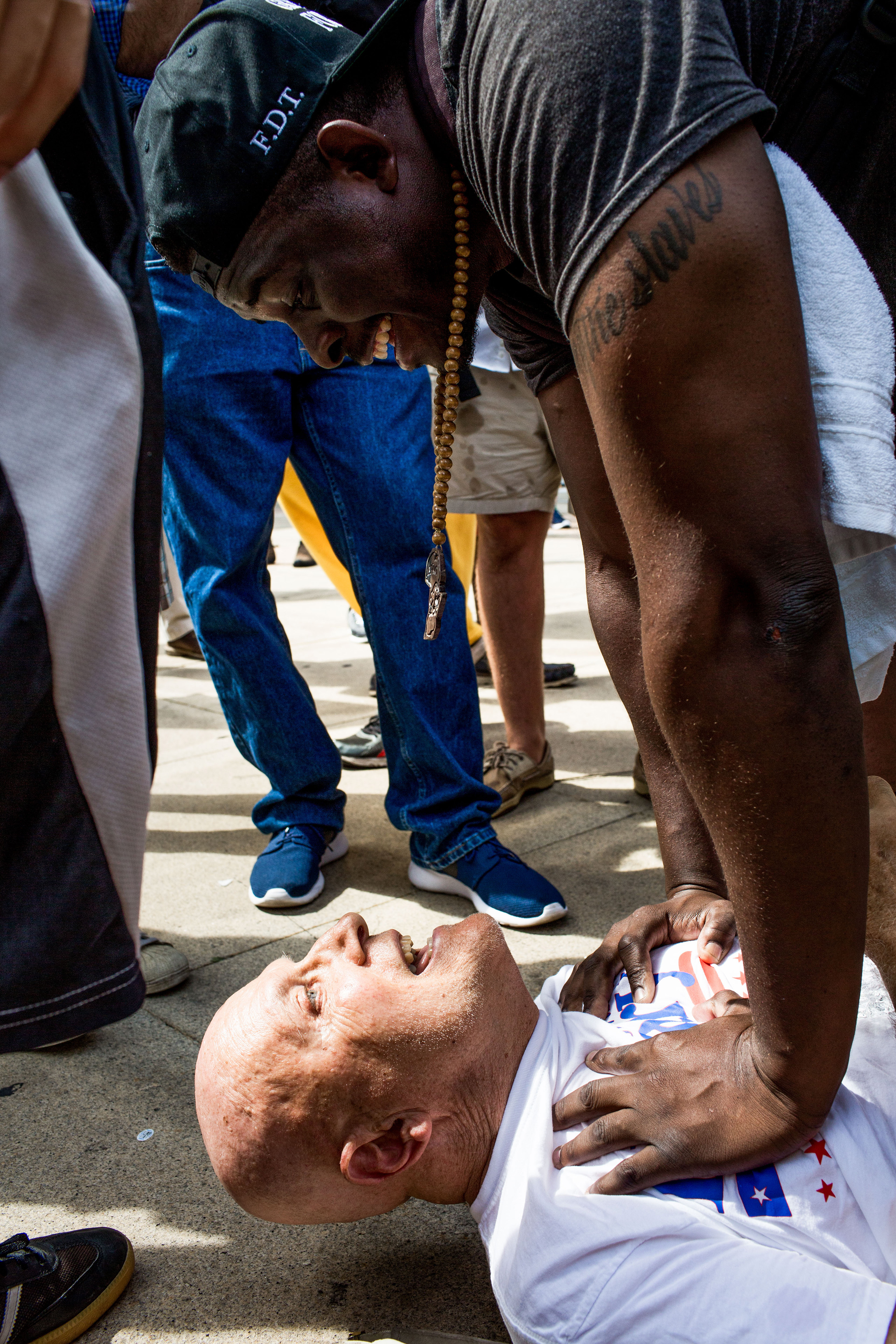 A man accused of assaulting a protestor is held down by another protestor until police arrive. Protesters convened at City Hall in Philadelphia on Tuesday afternoon to watch speaker Jill Stein and protest theDemocratic National Convention at the Wells Fargo Center on July 26, 2016.