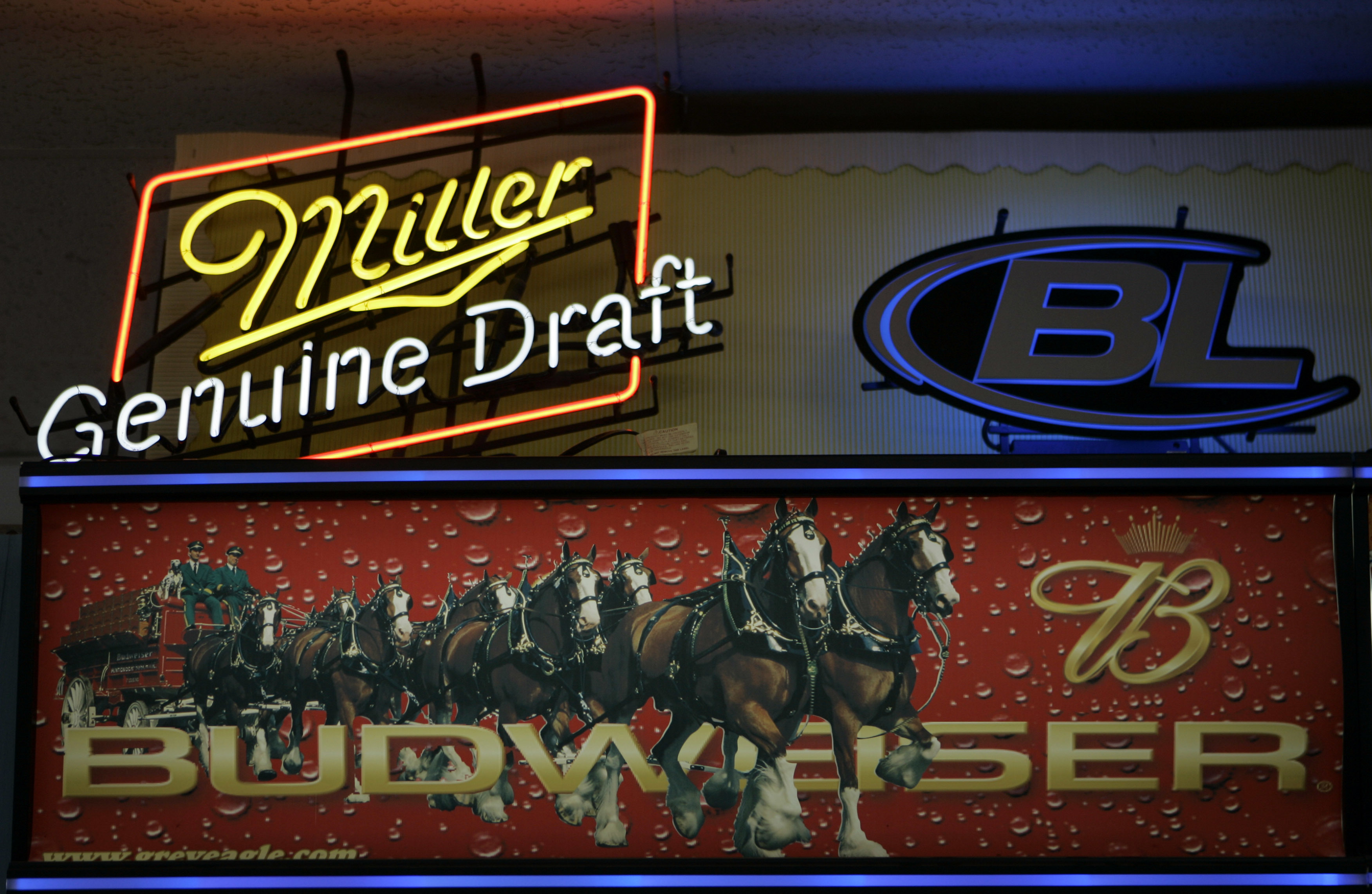 Signs for Miller and Anheuser-Busch products above a liquor store cooler in St. Louis.