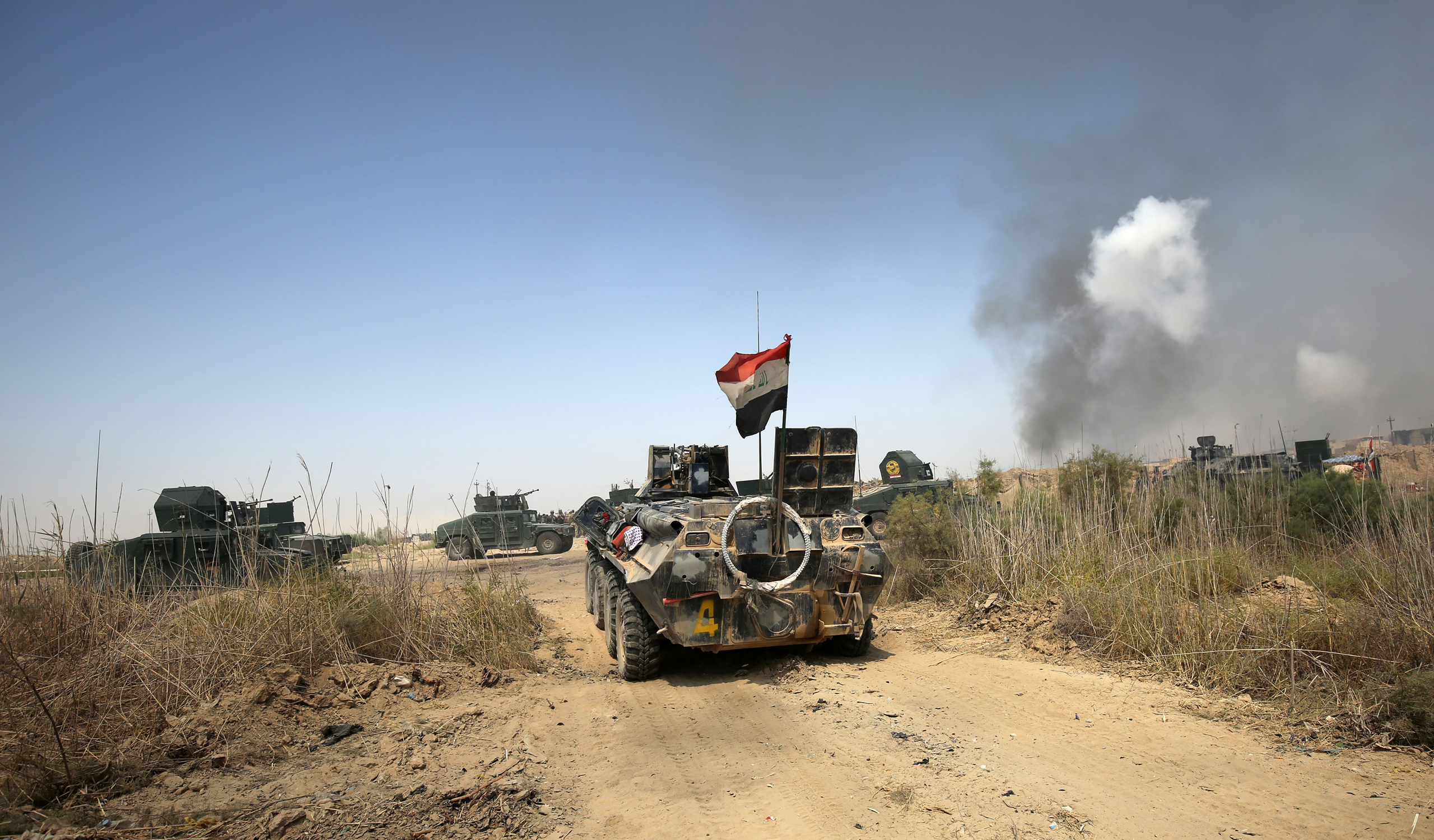Iraqi government forces drive their armoured vehicles during an operation, backed by air support from the US-led coalition, in Fallujah's southern Shuhada neighbourhood to retake the area from the Islamic State (IS) group on June 15, 2016.