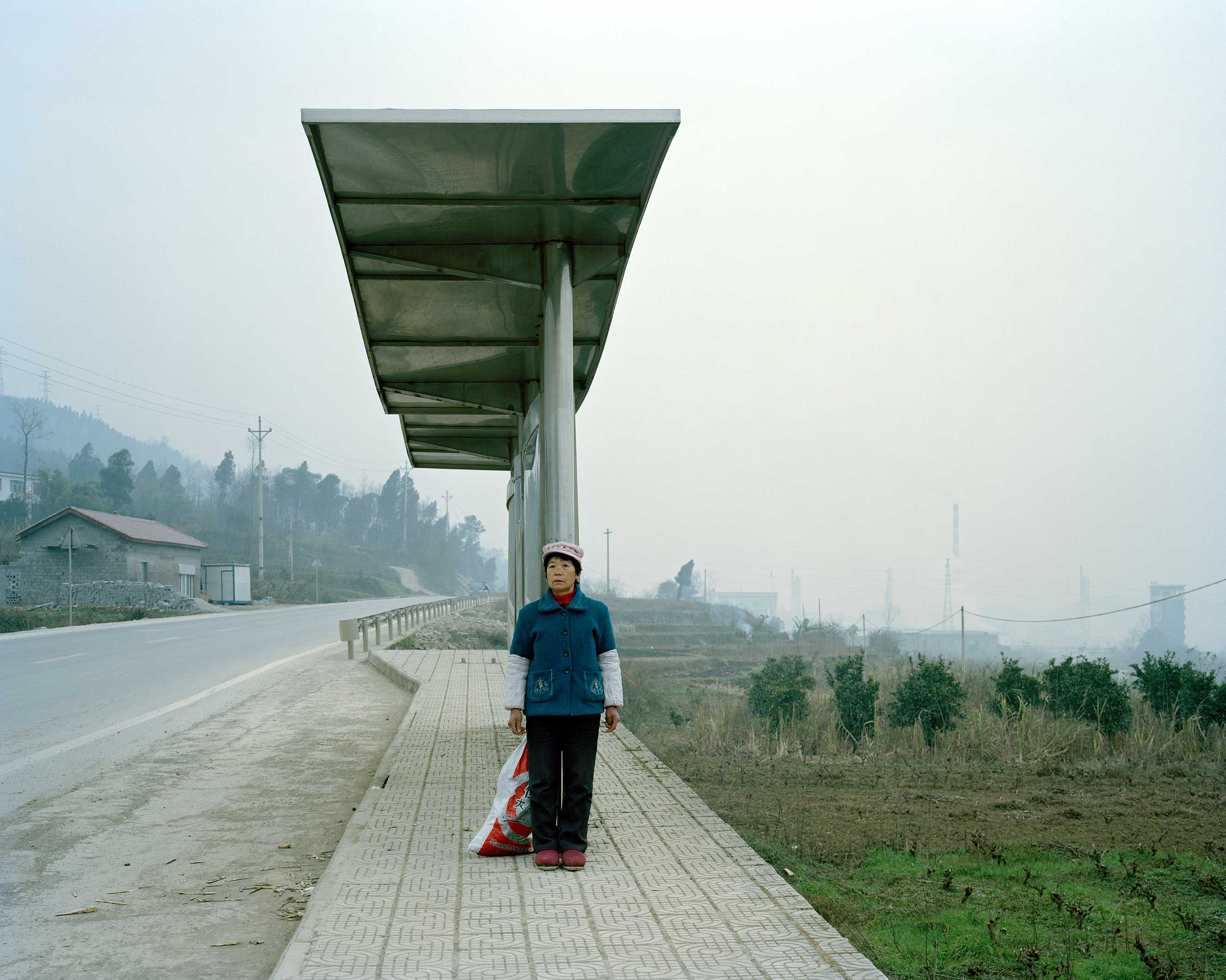Baitao village, China, January 2015. Ms Peng, who is 62 years old, waiting for the bus.