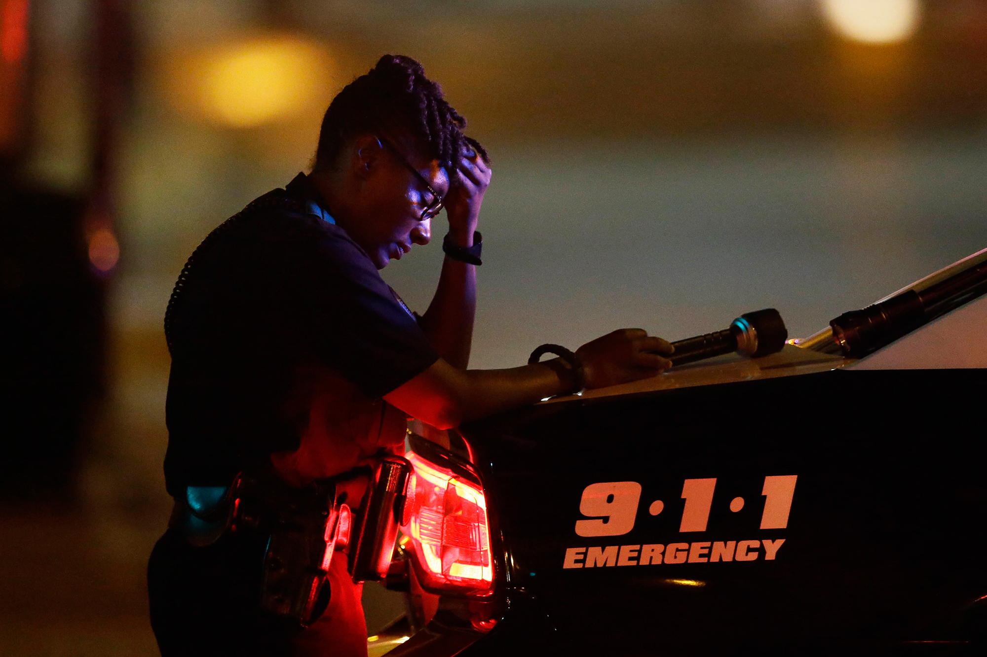 A Dallas police officer pauses for a moment in the early morning after a sniper shooting, which left five police officers dead, in Dallas, on July 8, 2016.