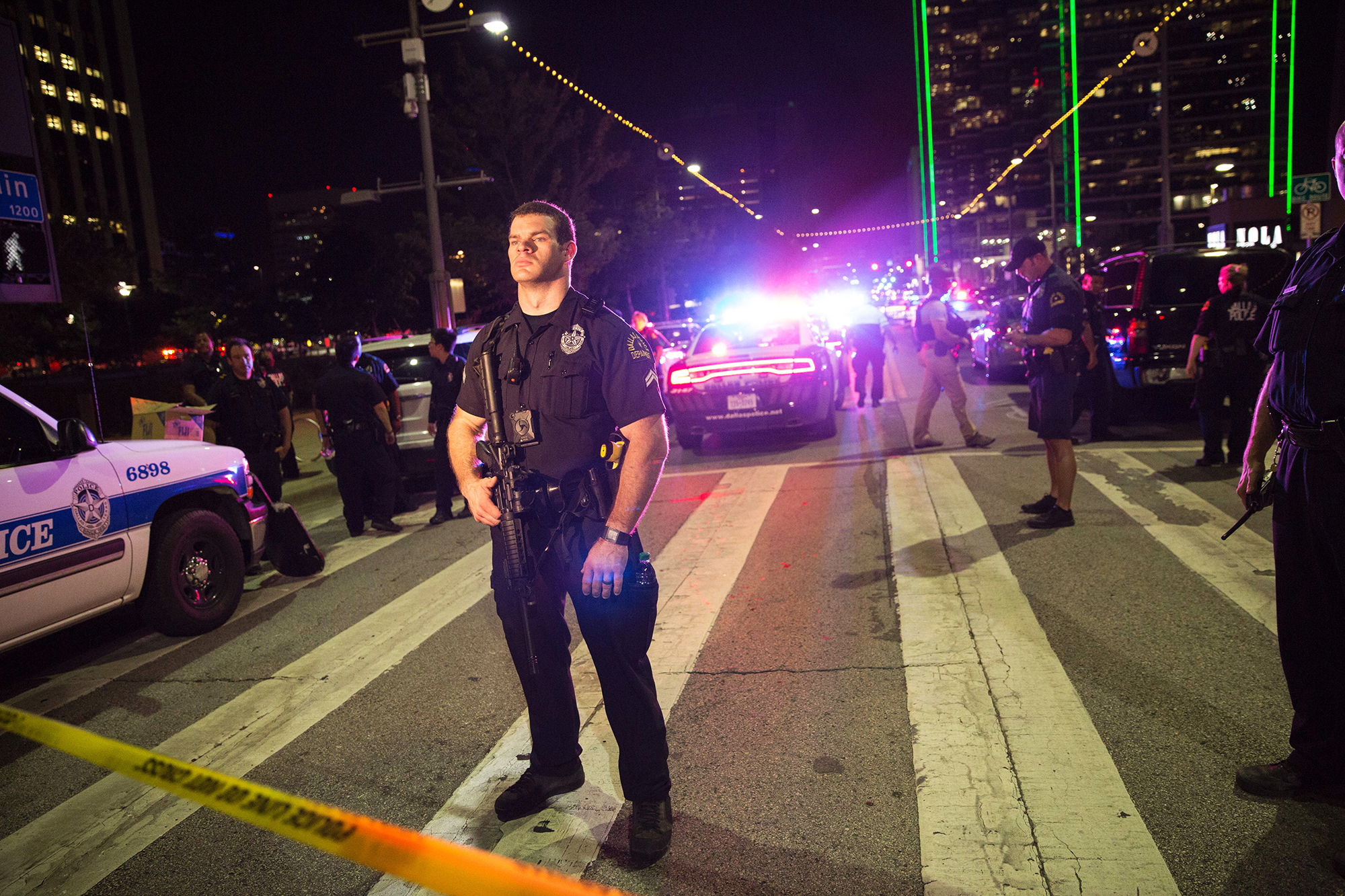 Police officers stand guard at a barricade following a sniper shooting in Dallas, on July 7, 2016.