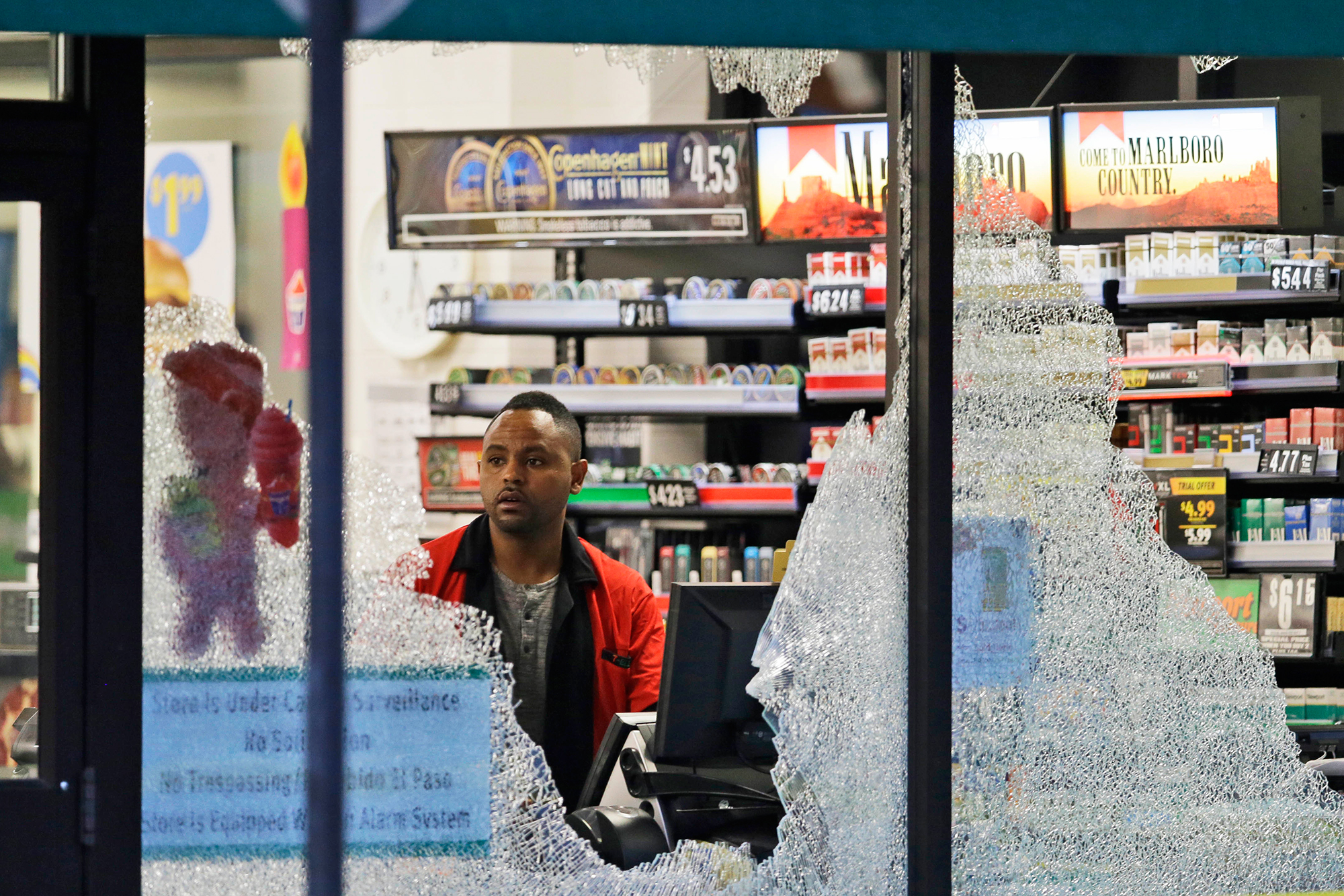 A clerk looks at a store's shattered windows after a sniper shooting in Dallas, on July 8, 2016.