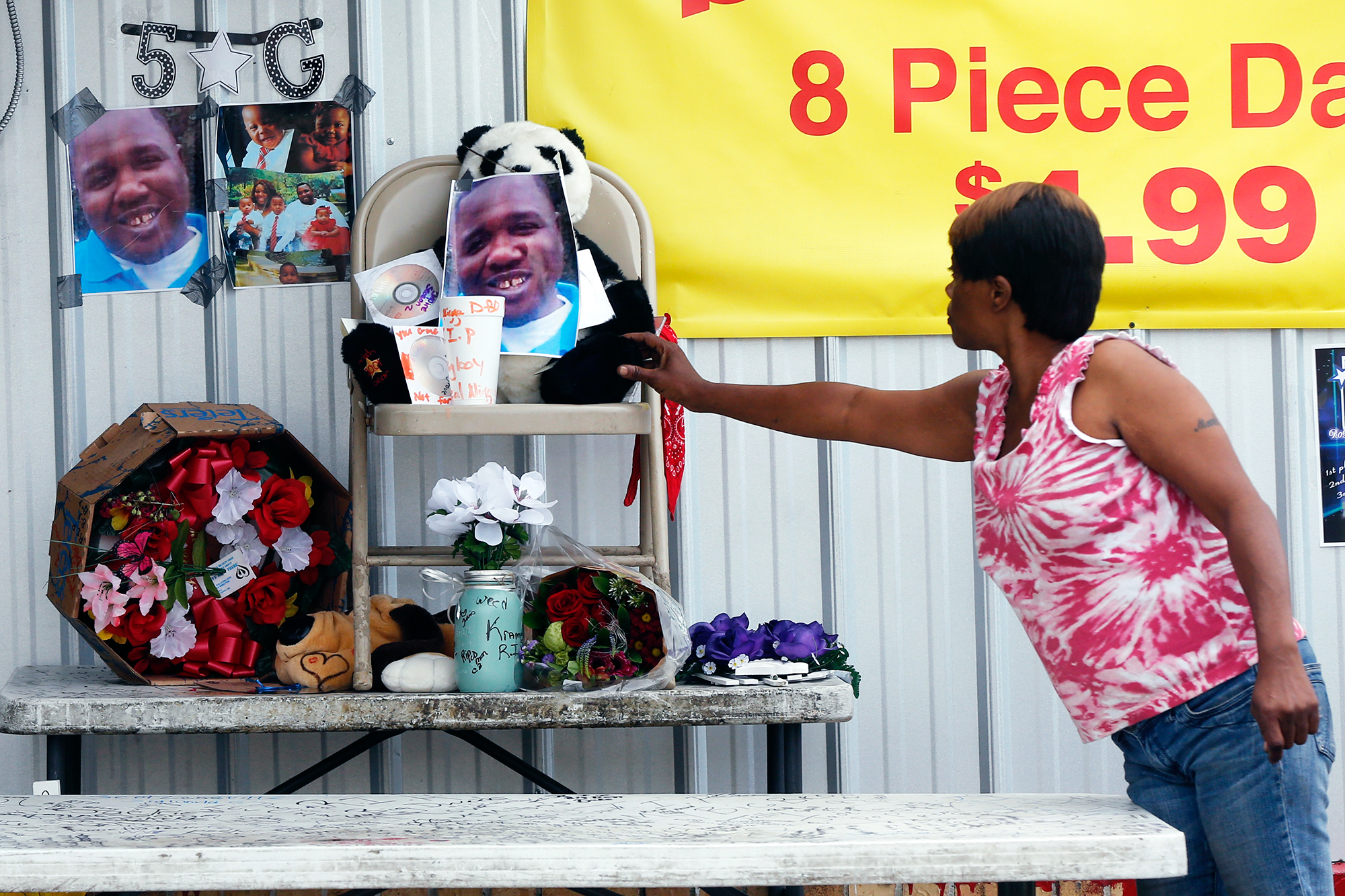 Nishka Johnson touches a makeshift memorial for Alton Sterling, in Baton Rouge, La., on July 6, 2016.