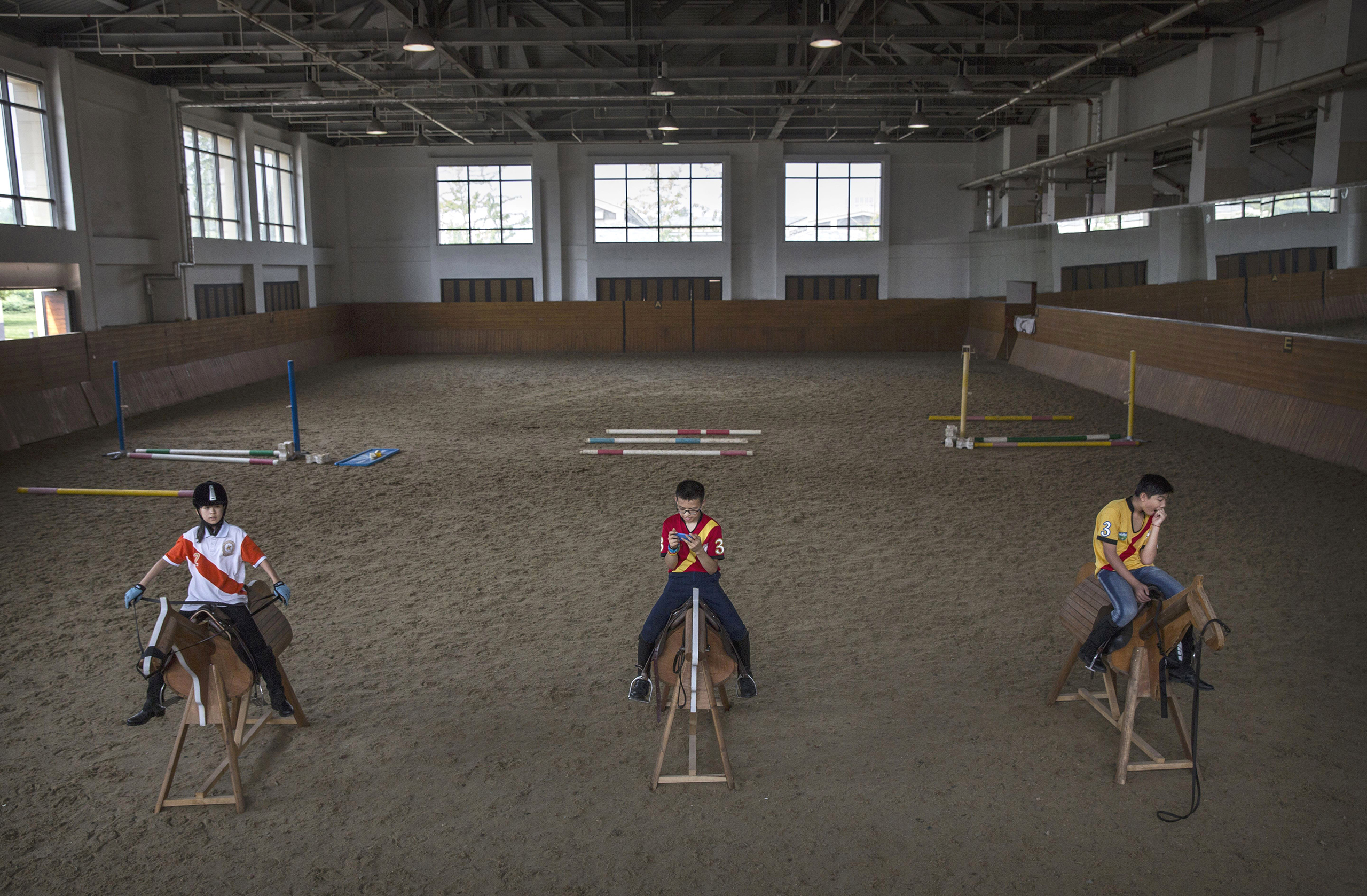 Young Chinese players from the Junior Polo Program sit on wooden horses at a summer training camp held at the Tianjin Goldin Metropolitan Polo Club in Tianjin, China, on July 16, 2016.