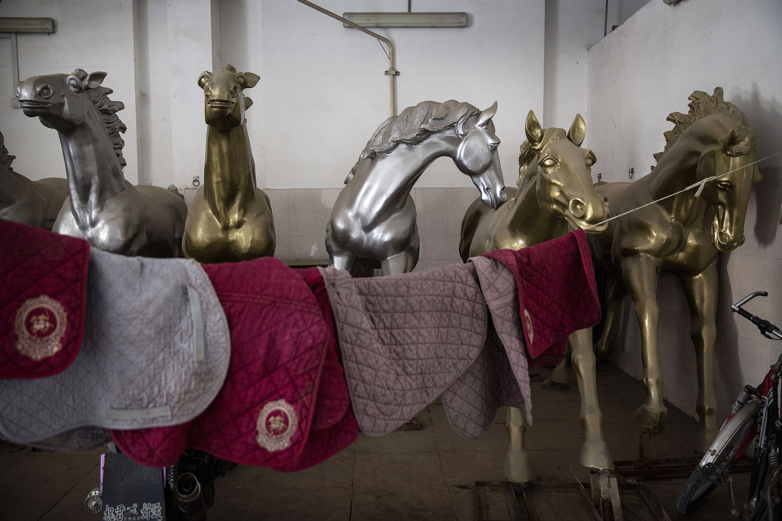 Painted horse sculptures are seen in the stables at the Tianjin Goldin Metropolitan Polo Club in Tianjin, China, on July 16, 2016.