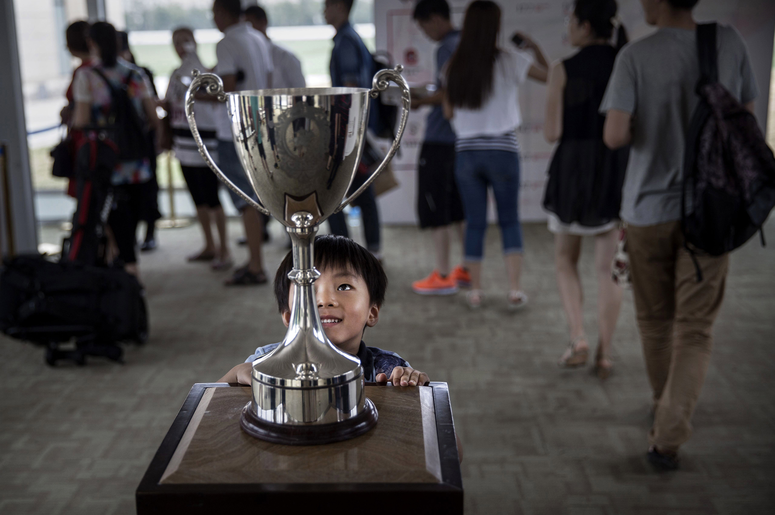 A boy looks at the cup before a match at the Tianjin Goldin Metropolitan Polo Club in Tianjin, China, on July 17, 2016.